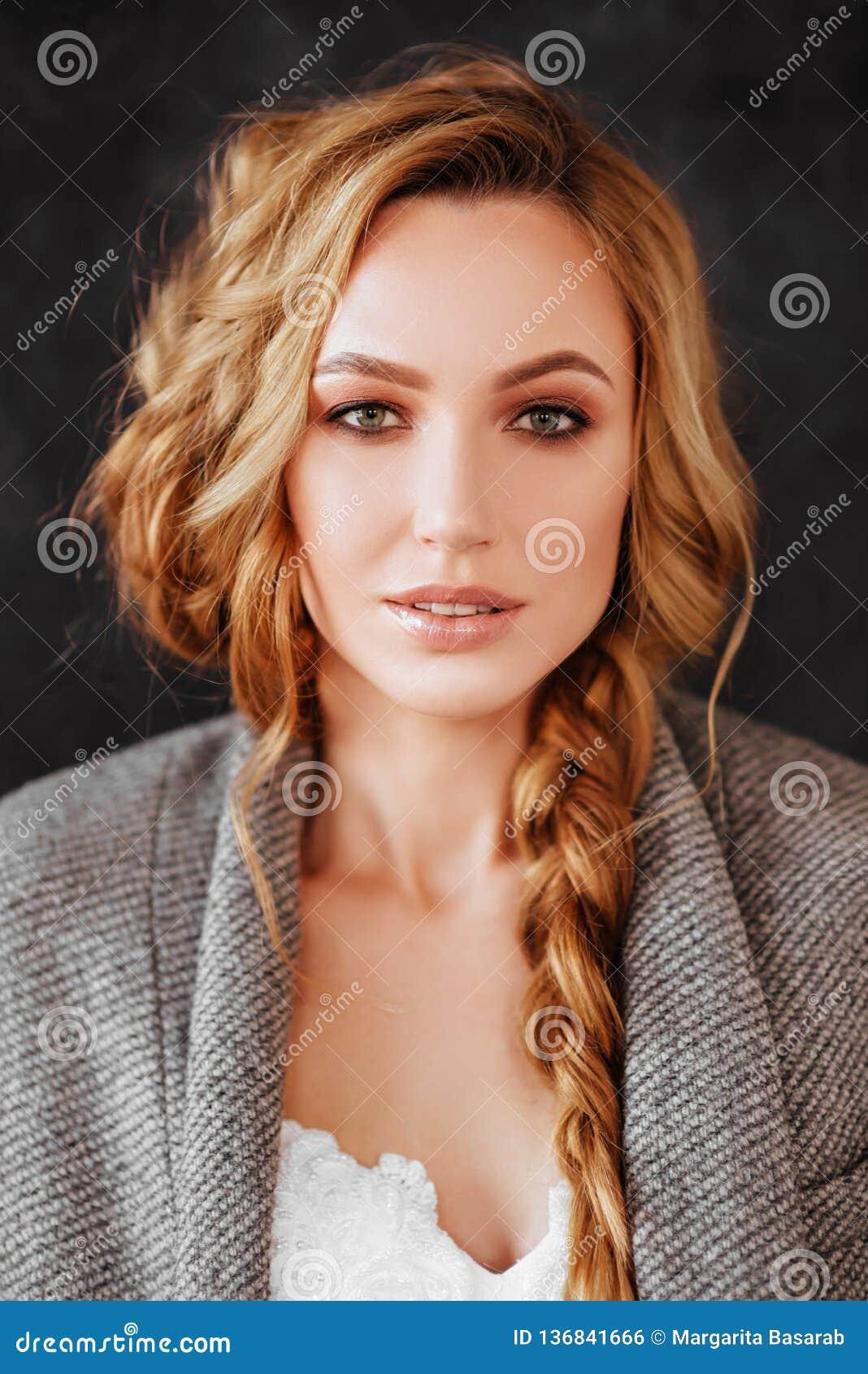 Het mooie het glimlachen model van de blondevrouw in modieuze donkere overjas en witte kleding