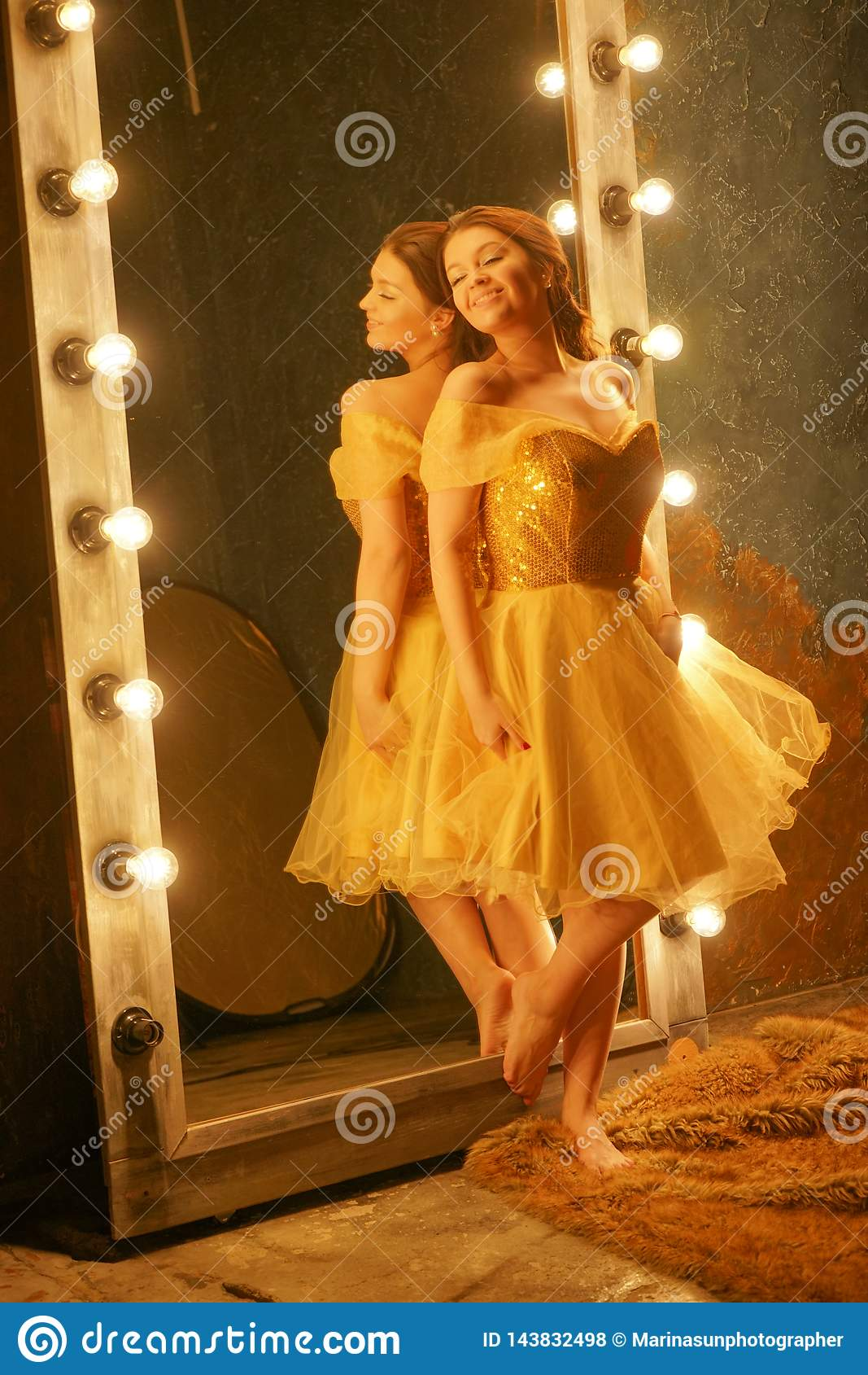 Het mooie jonge meisje in een gouden avondjurk bevindt zich op een bontdeken dichtbij een grote spiegel in een kader met lichten
