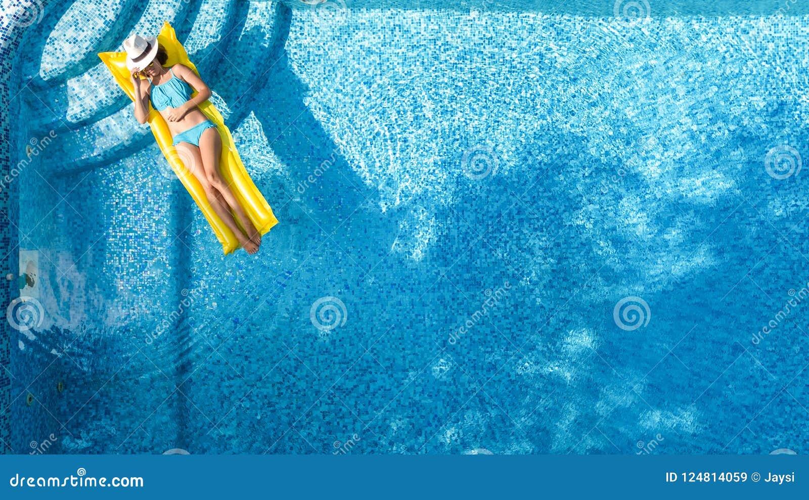 Het mooie jonge meisje ontspannen in zwembad, zwemt op opblaasbare matras en heeft pret in water op familievakantie