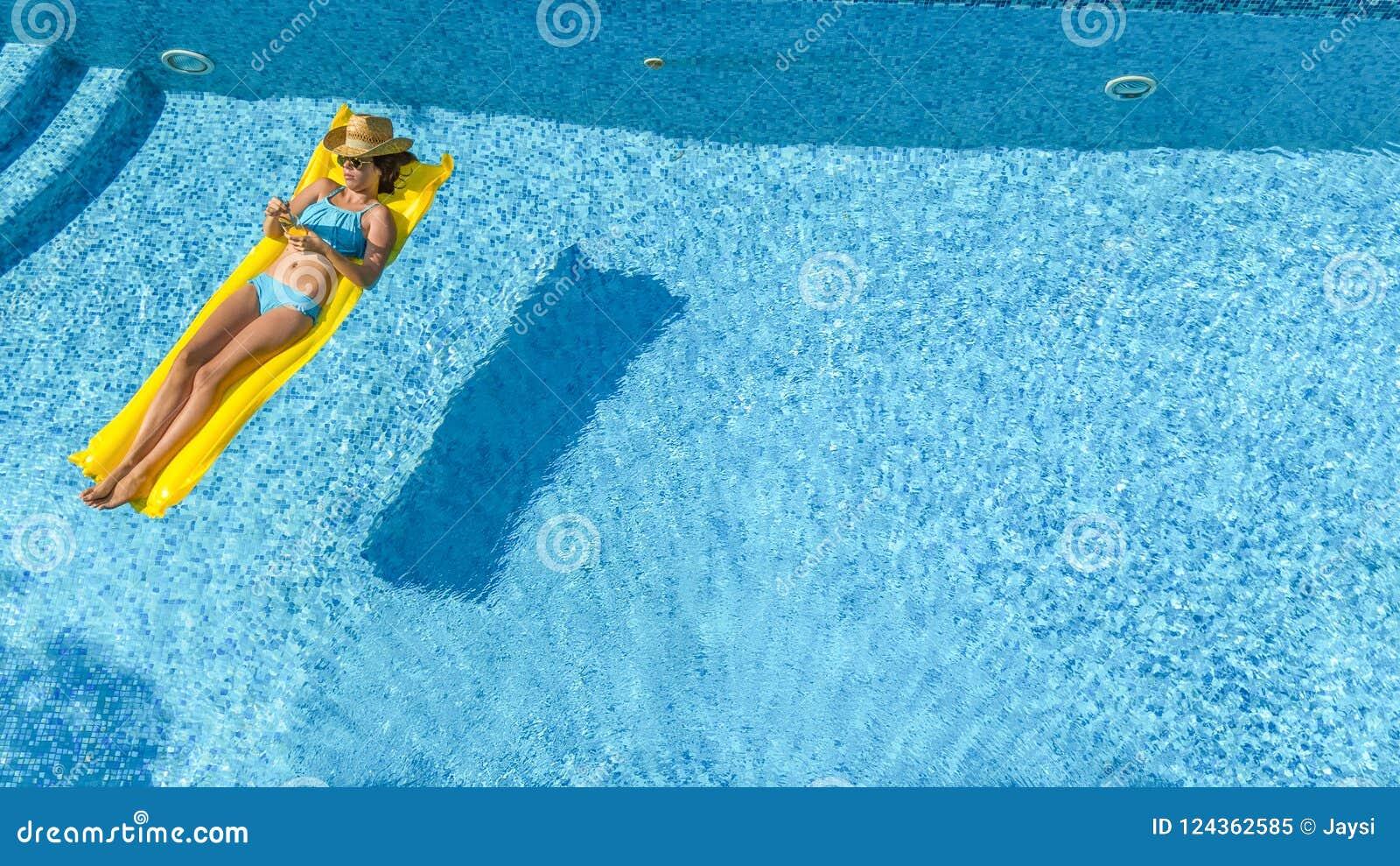 Het mooie jonge meisje ontspannen in zwembad, zwemt op opblaasbare matras en heeft pret in water op familievakantie, luchtmening