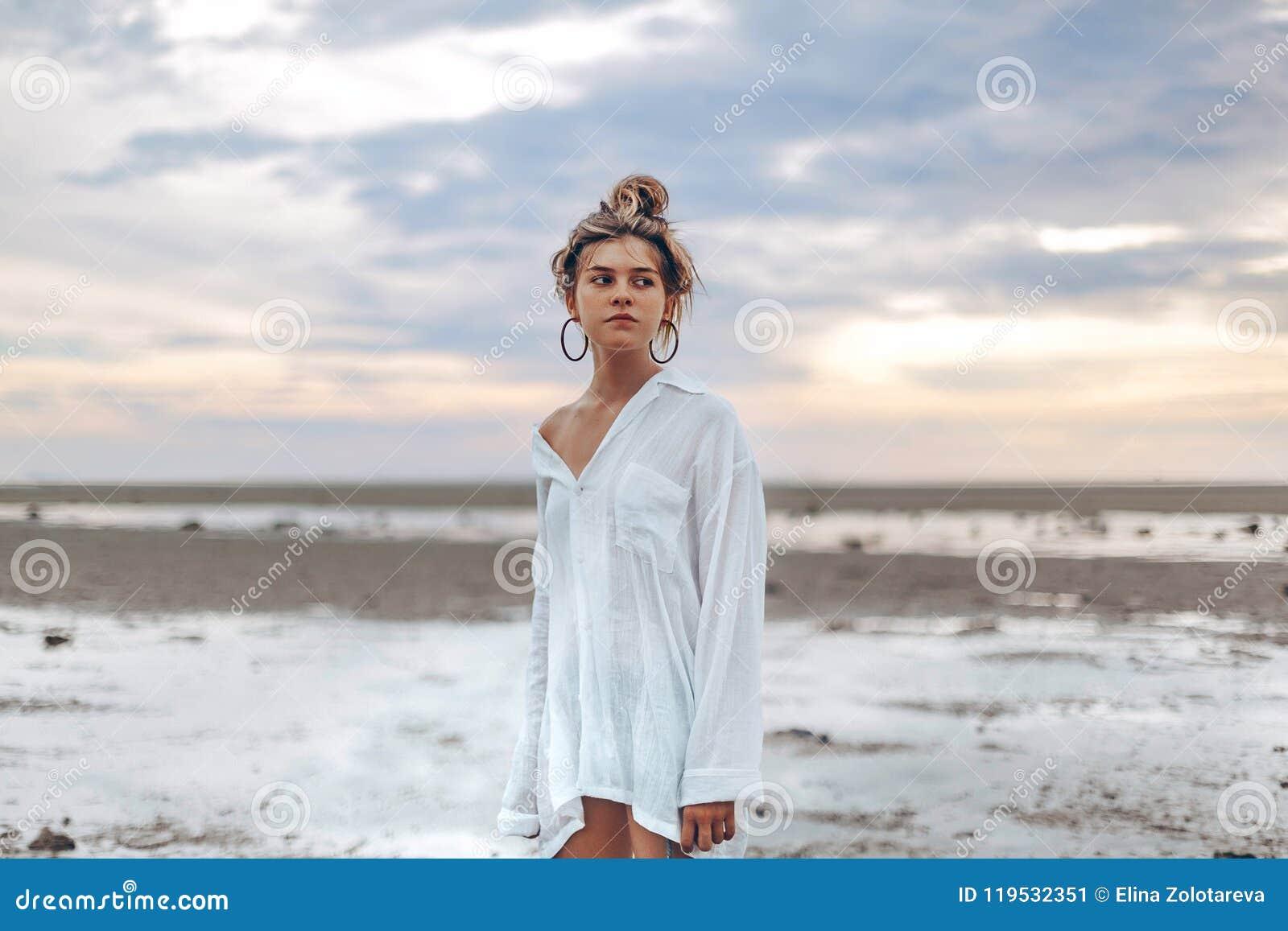 Het mooie jonge meisje van de bohostijl op het strand bij zonsondergang jong Na