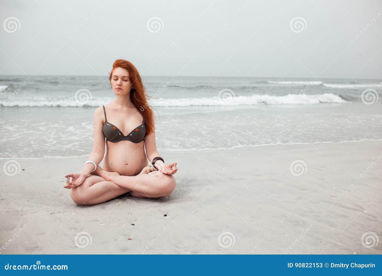 Het mooie jonge roodharige zwangere meisje mediteert in de lotusbloempositie inzake de achtergrond van het overzees Een gezonde m