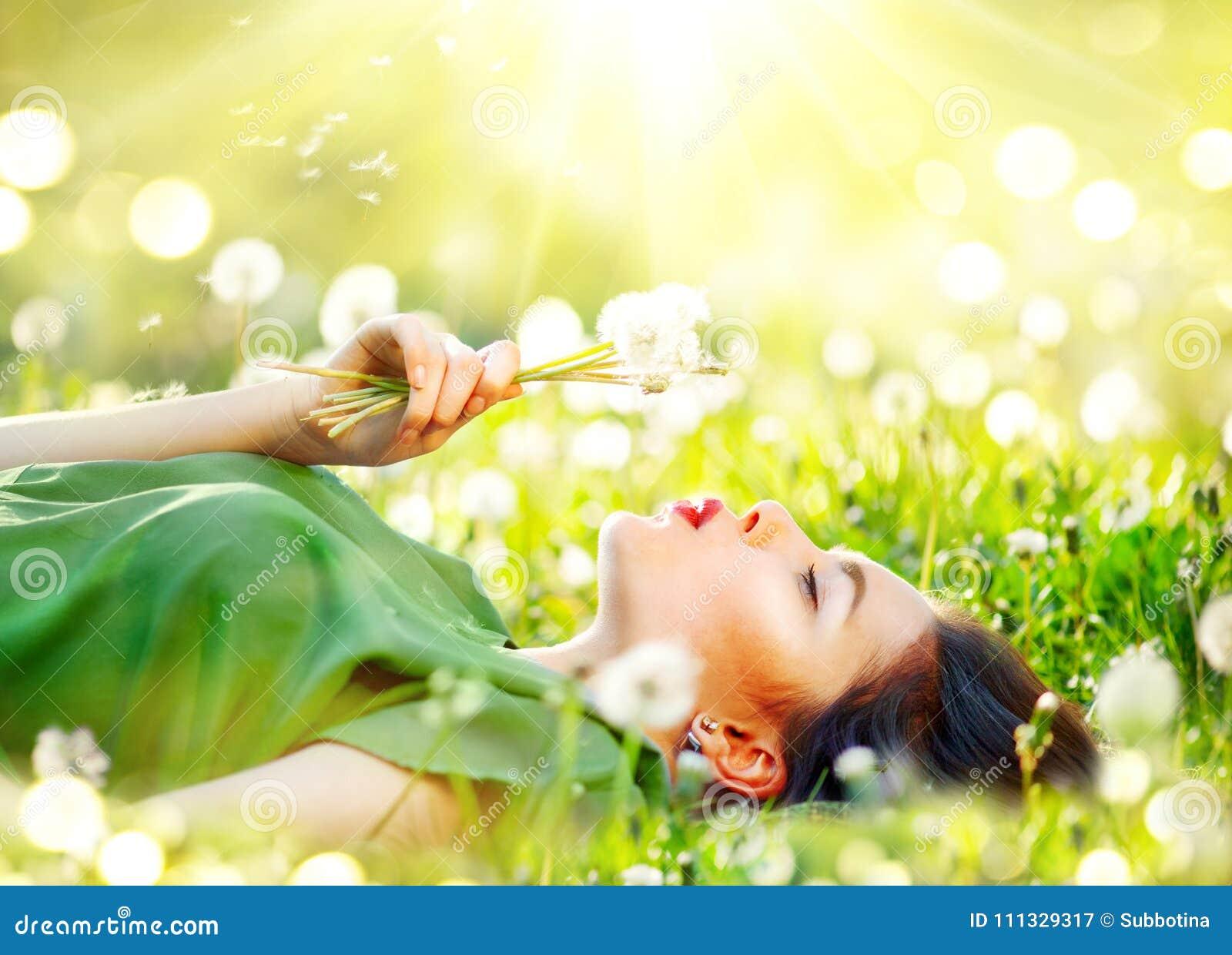 Het mooie jonge vrouw liggen op het gebied in groen gras en blazende paardebloem bloeit