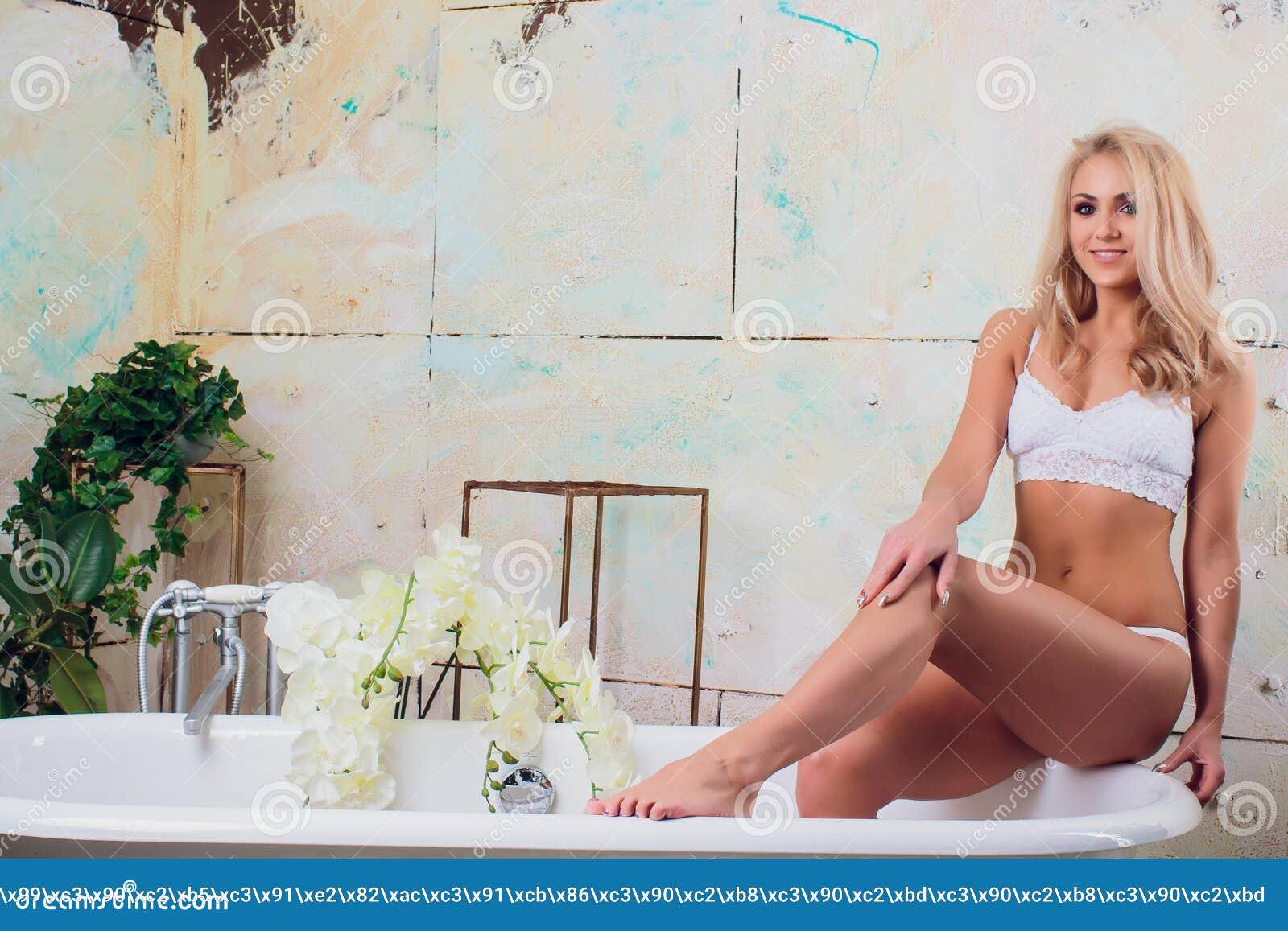 Het mooie jonge vrouw ontspannen die in bathtube liggen