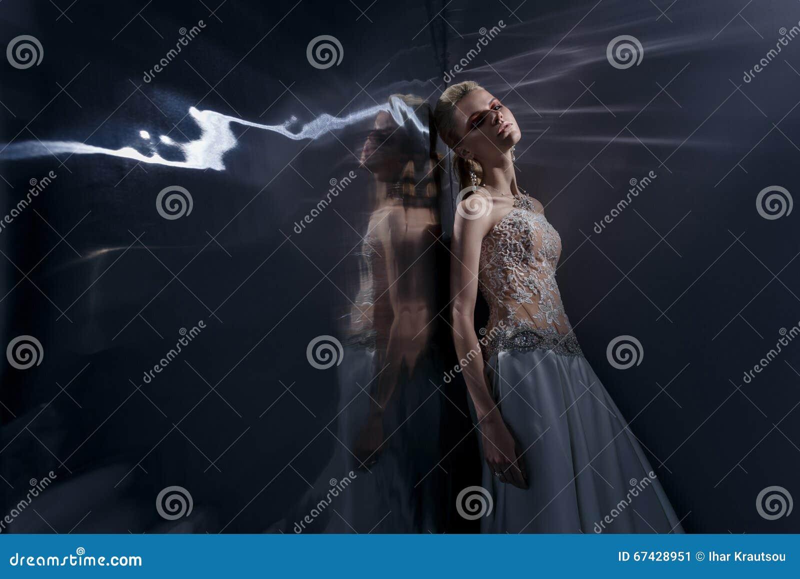 Het mooie jonge vrouw stellen in een huwelijkskleding
