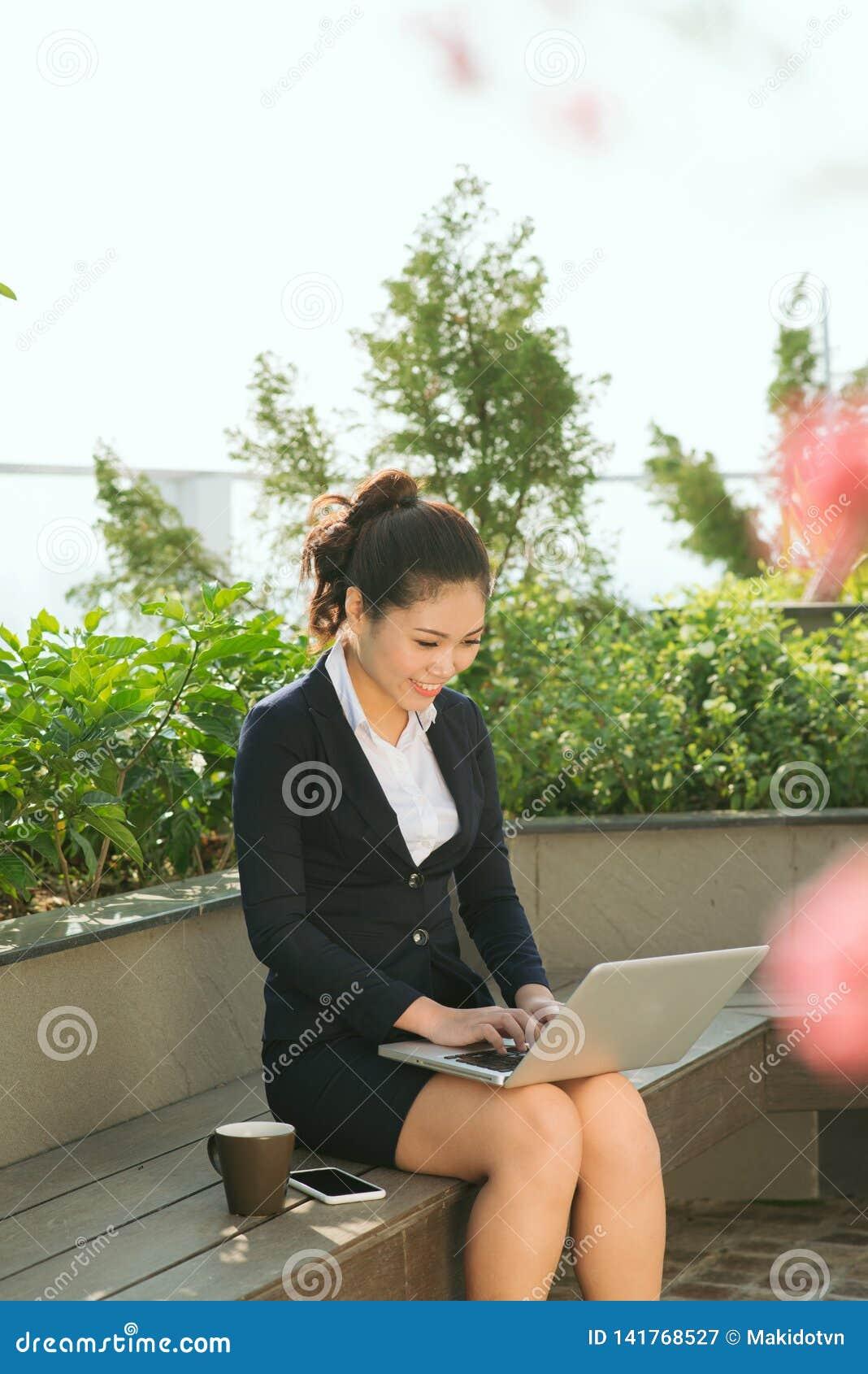 Het mooie leuke meisje glimlachen in bedrijfsvrouw kleedt het gebruiken van laptop computer in het park
