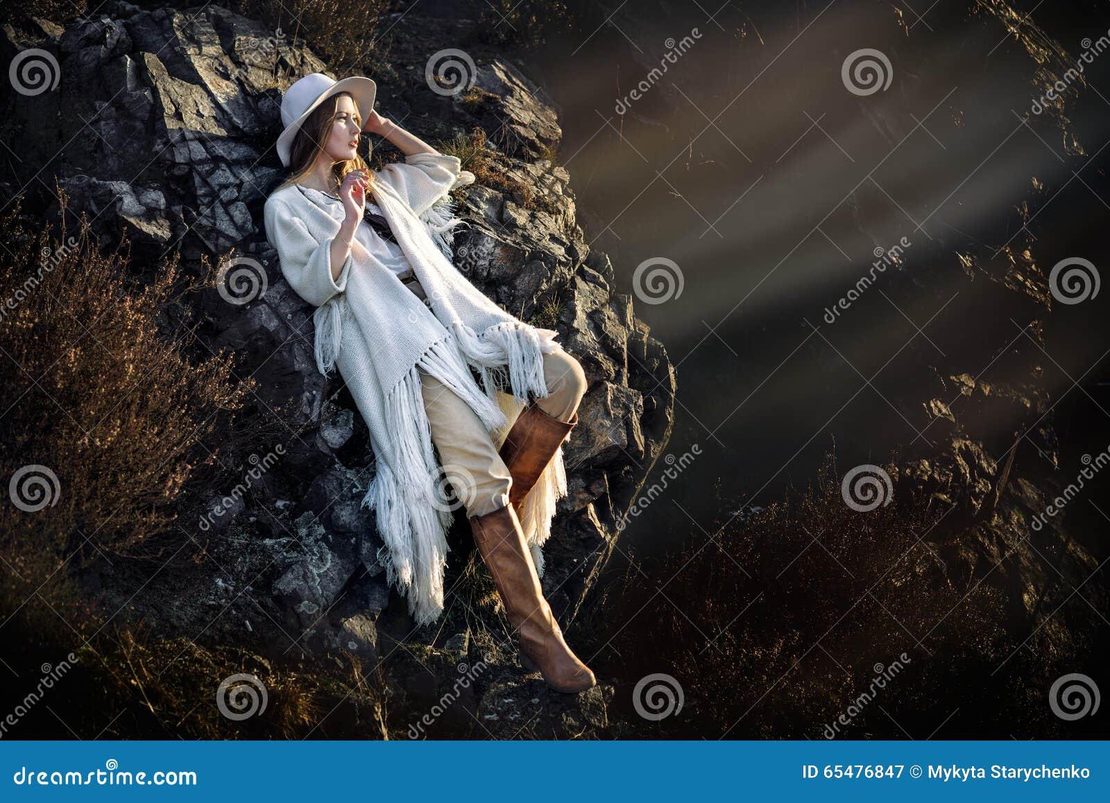 Het mooie mannequinvrouw stellen in bergen bij zonsondergang