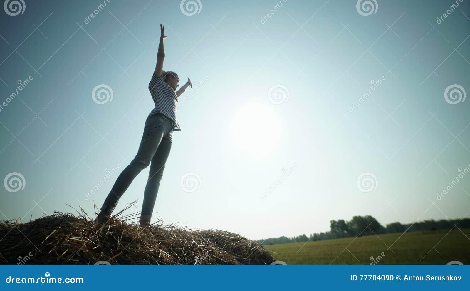 Het mooie meisje bevindt zich op hooibergen en trekt handen aan de hemel