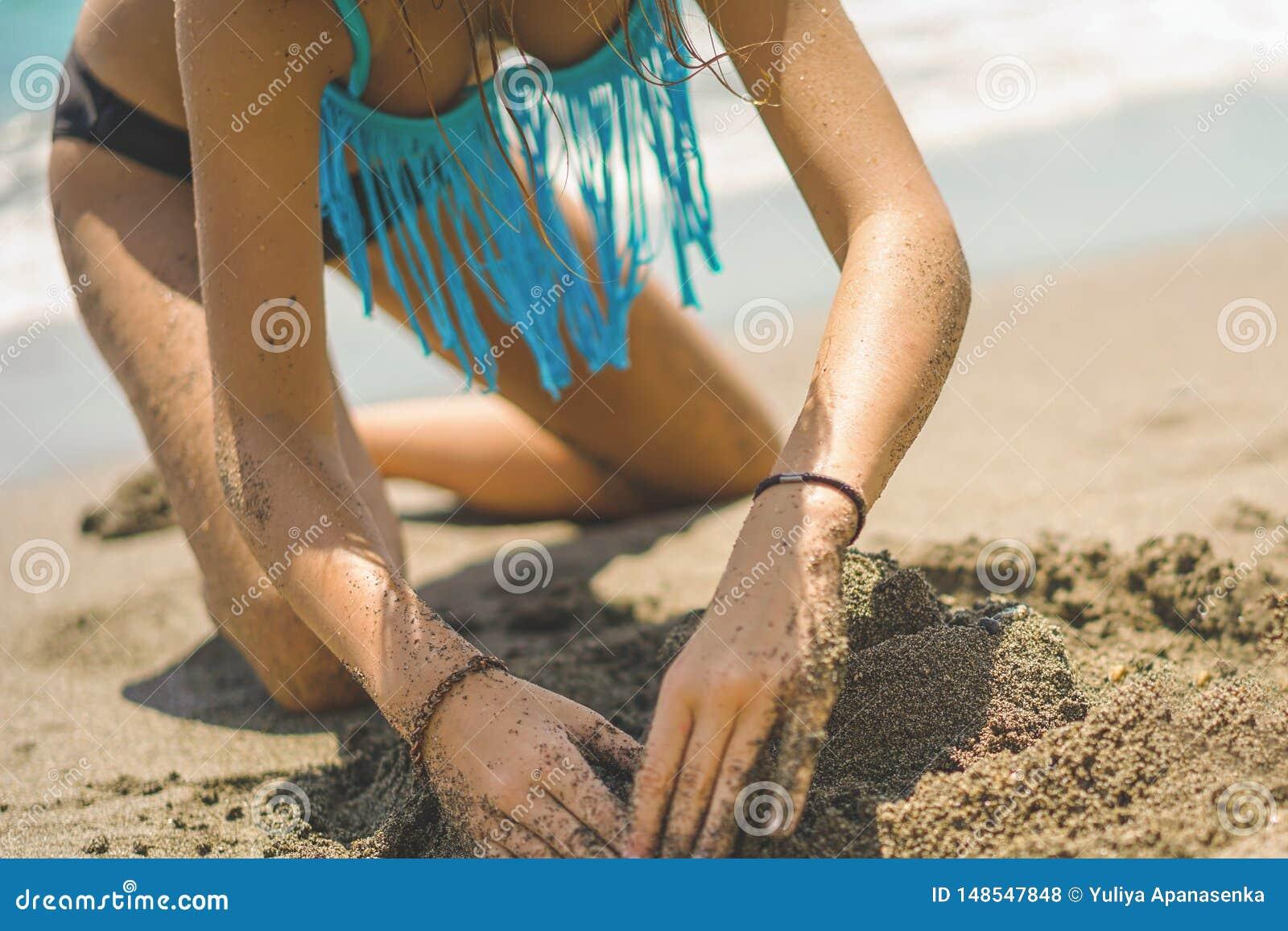 Het mooie meisje in bikini bouwt een zandkasteel op het strand
