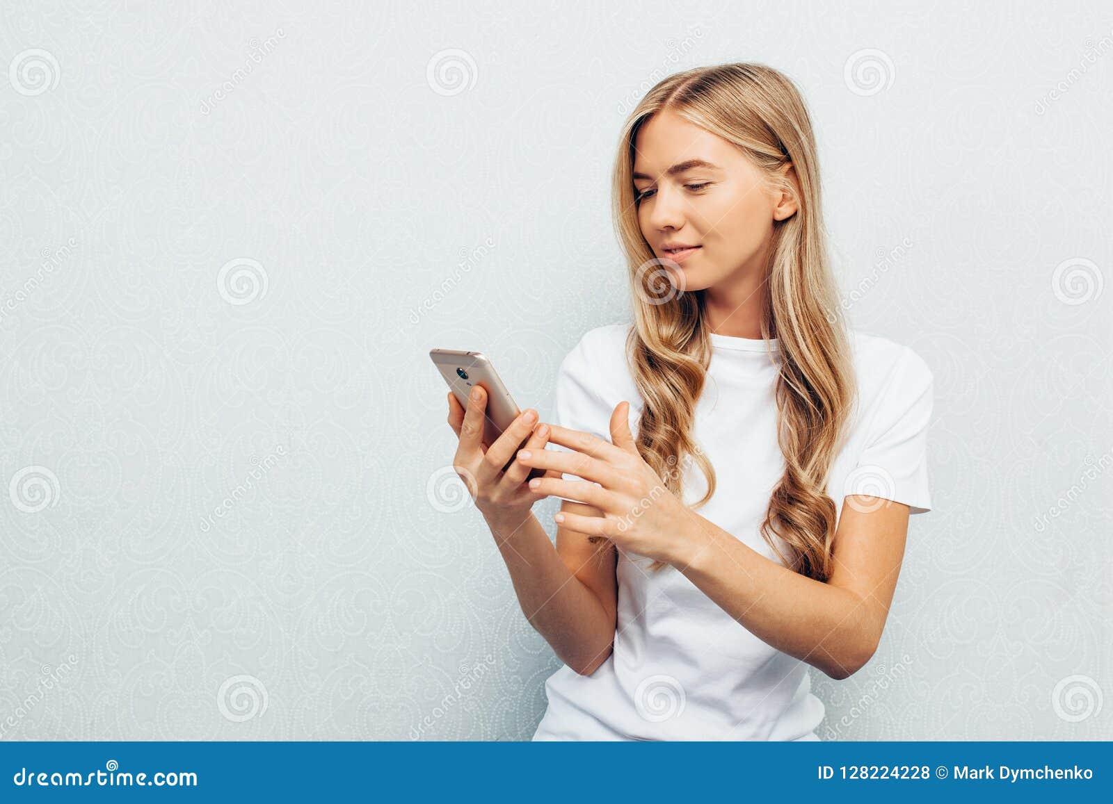 Het mooie meisje die wit overhemd dragen, het houden telefoneert en bekijken die die het scherm, op vloer, benen zitten, op grijz