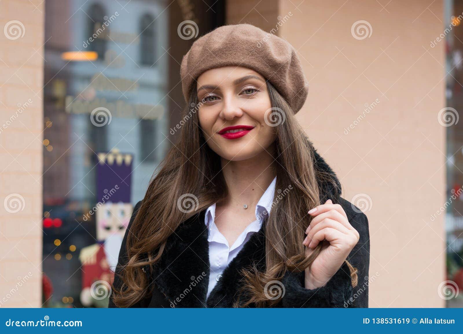 Het mooie meisje in een baret bevindt zich dichtbij de vensterkoffie