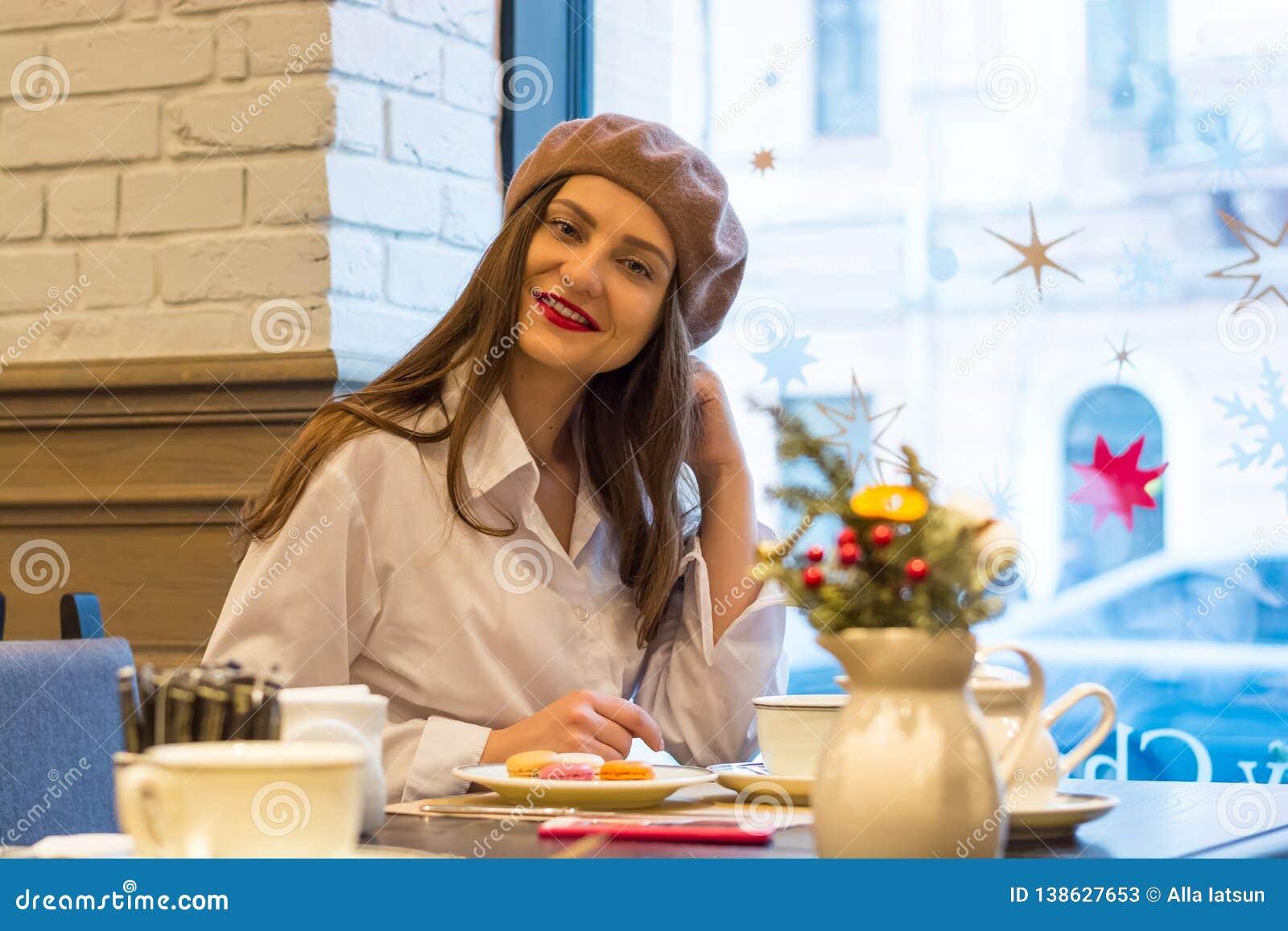 Het mooie meisje in een baret zit bij een lijst in een koffie met een kop thee, makarons