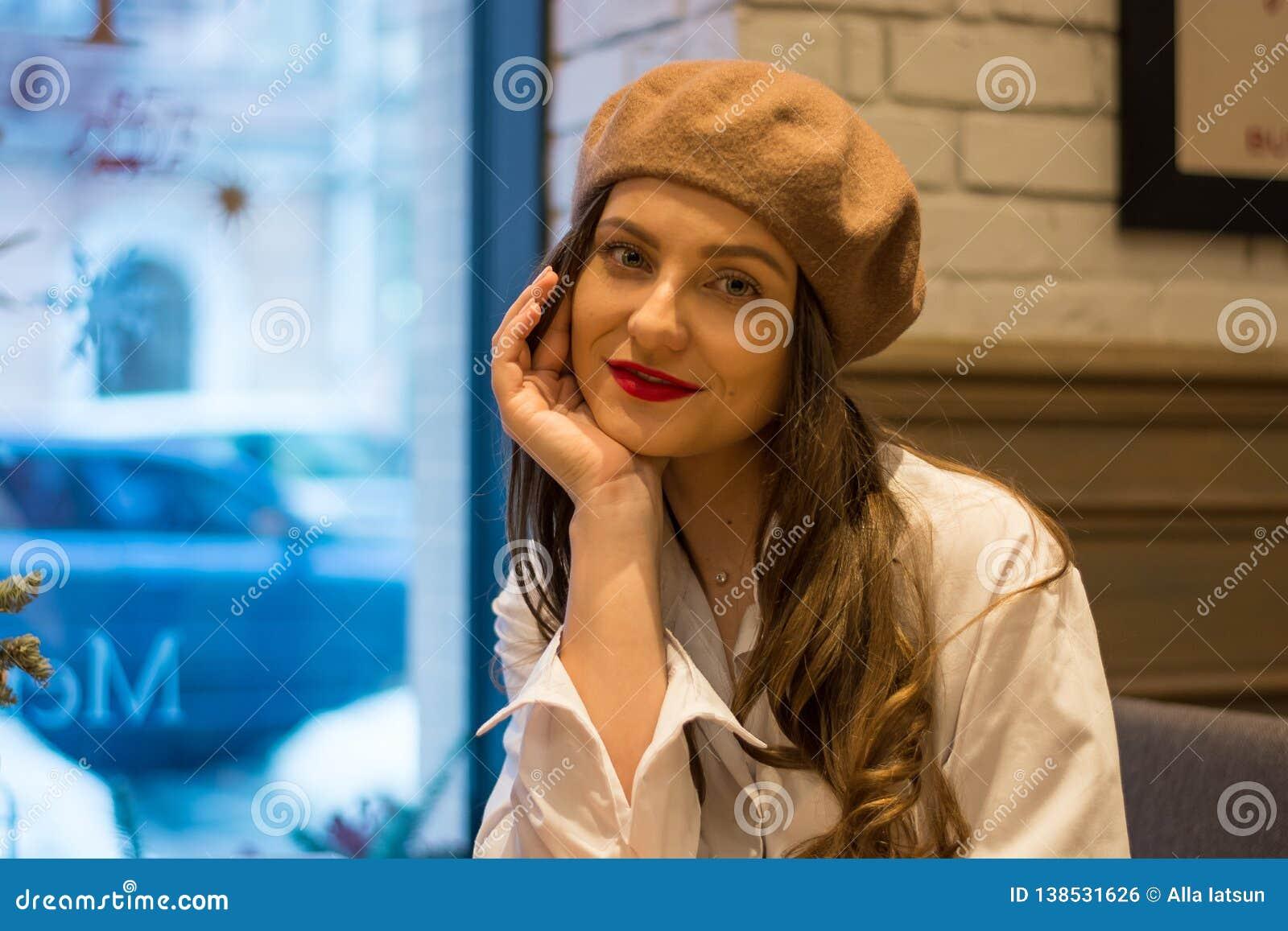 Het mooie meisje in een baret zit dichtbij het venster in een koffie