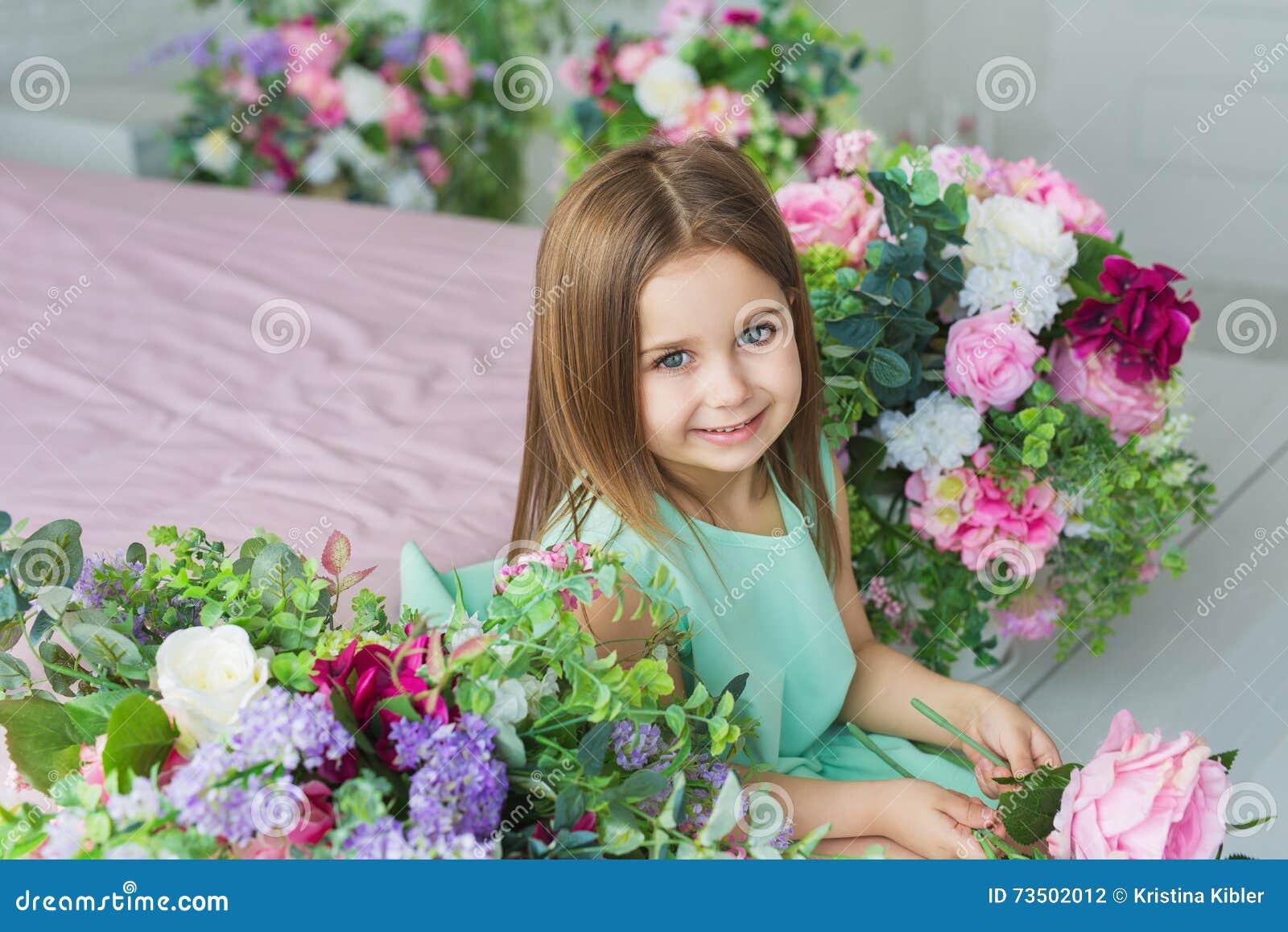 Het mooie meisje in een turkooise kleding zit en glimlacht dichtbij bloemen in een studio