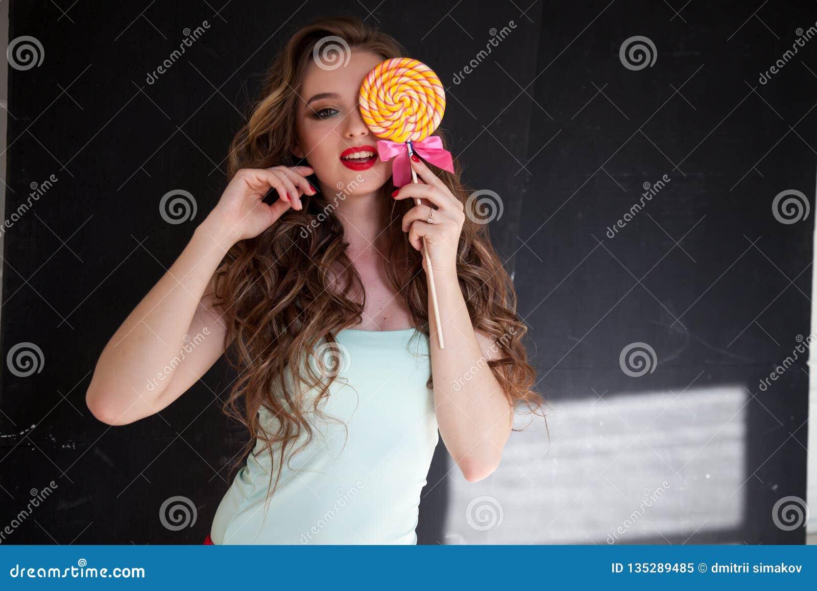 Het mooie meisje eet een suikergoed van de suikergoed zoet lolly