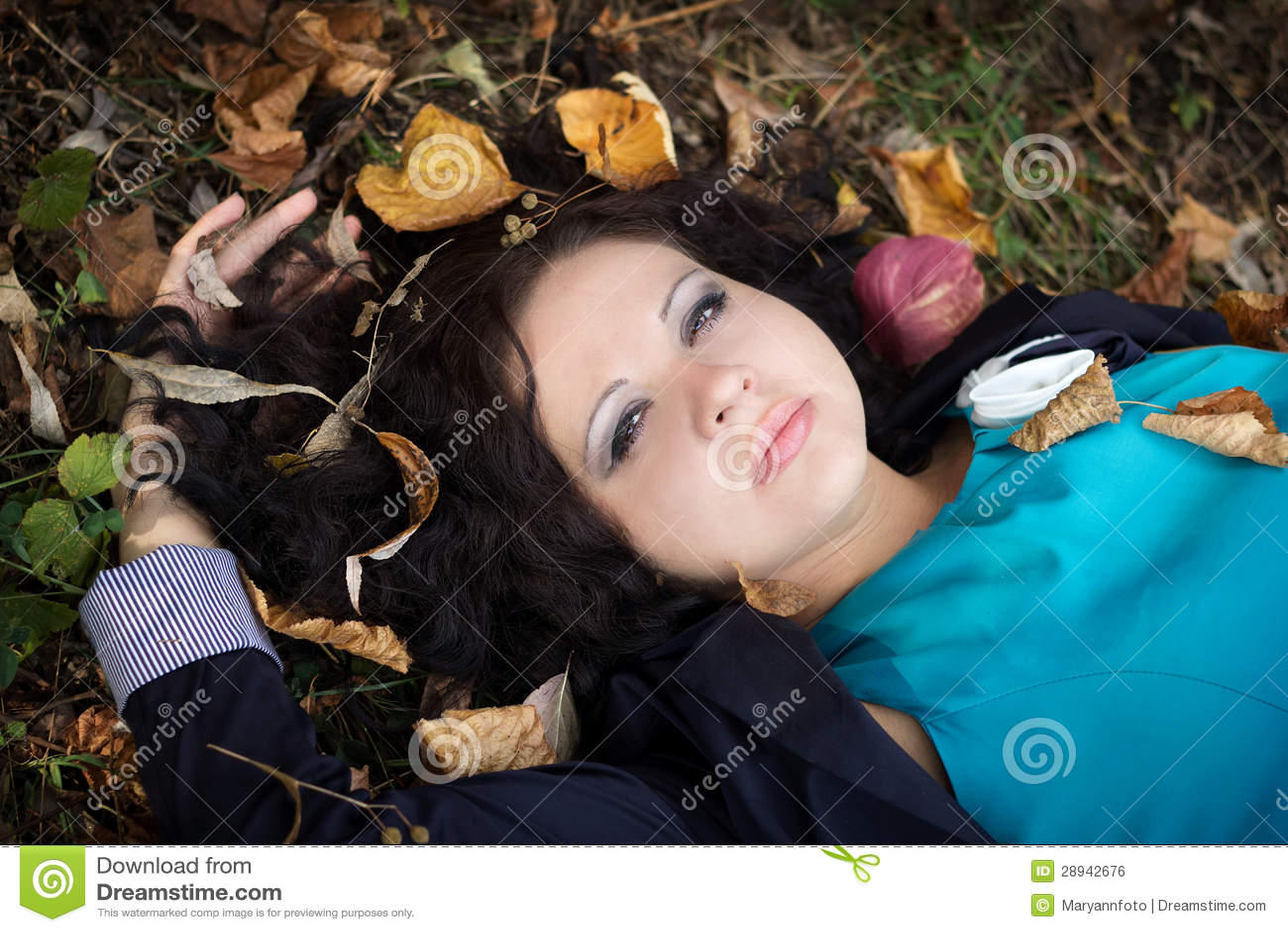 Het mooie meisje ligt op een gras