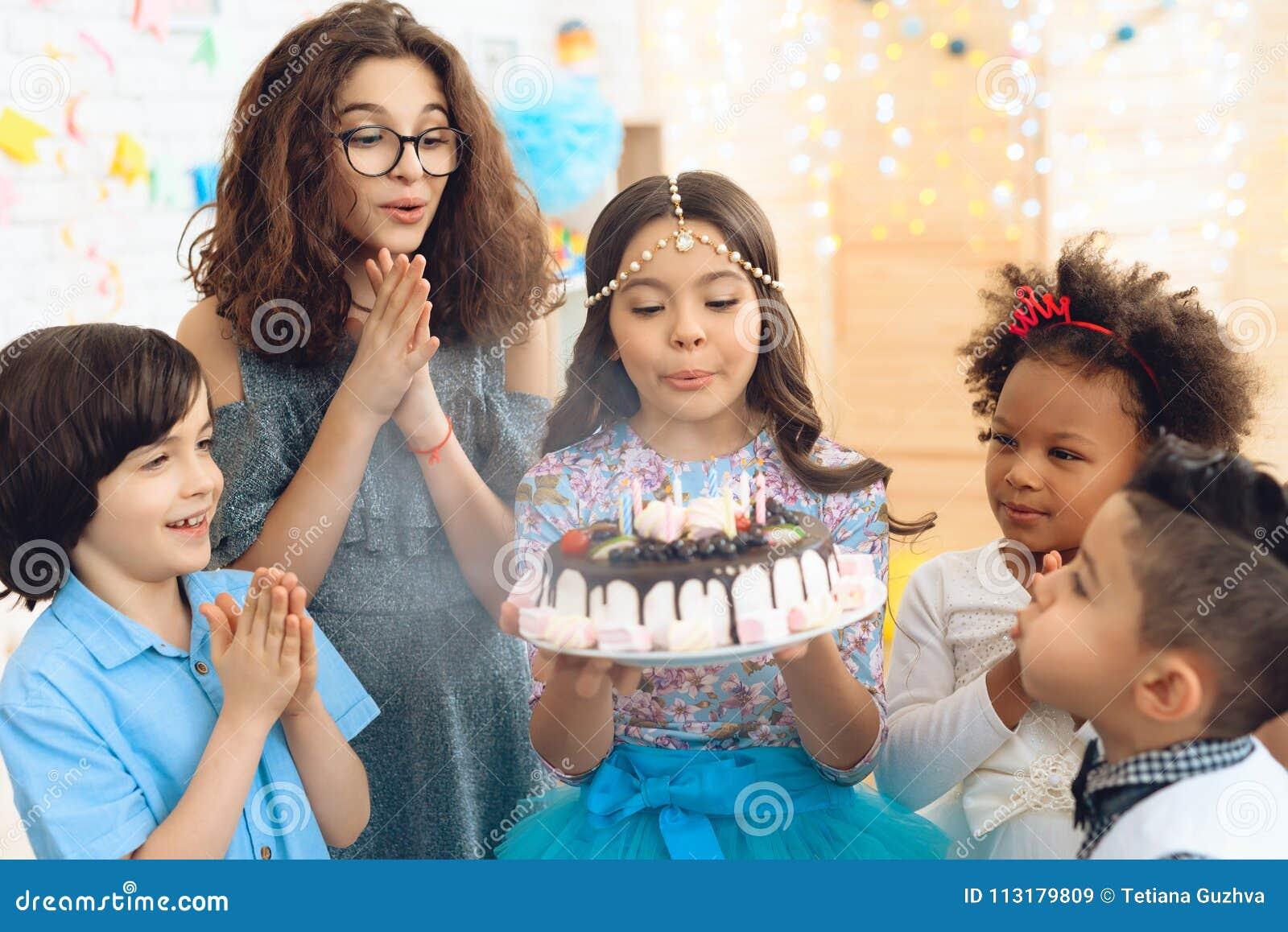 Het mooie meisje met hoofddeksel op hoofd blaast uit kaarsen op verjaardagscake Gelukkige verjaardagspartij