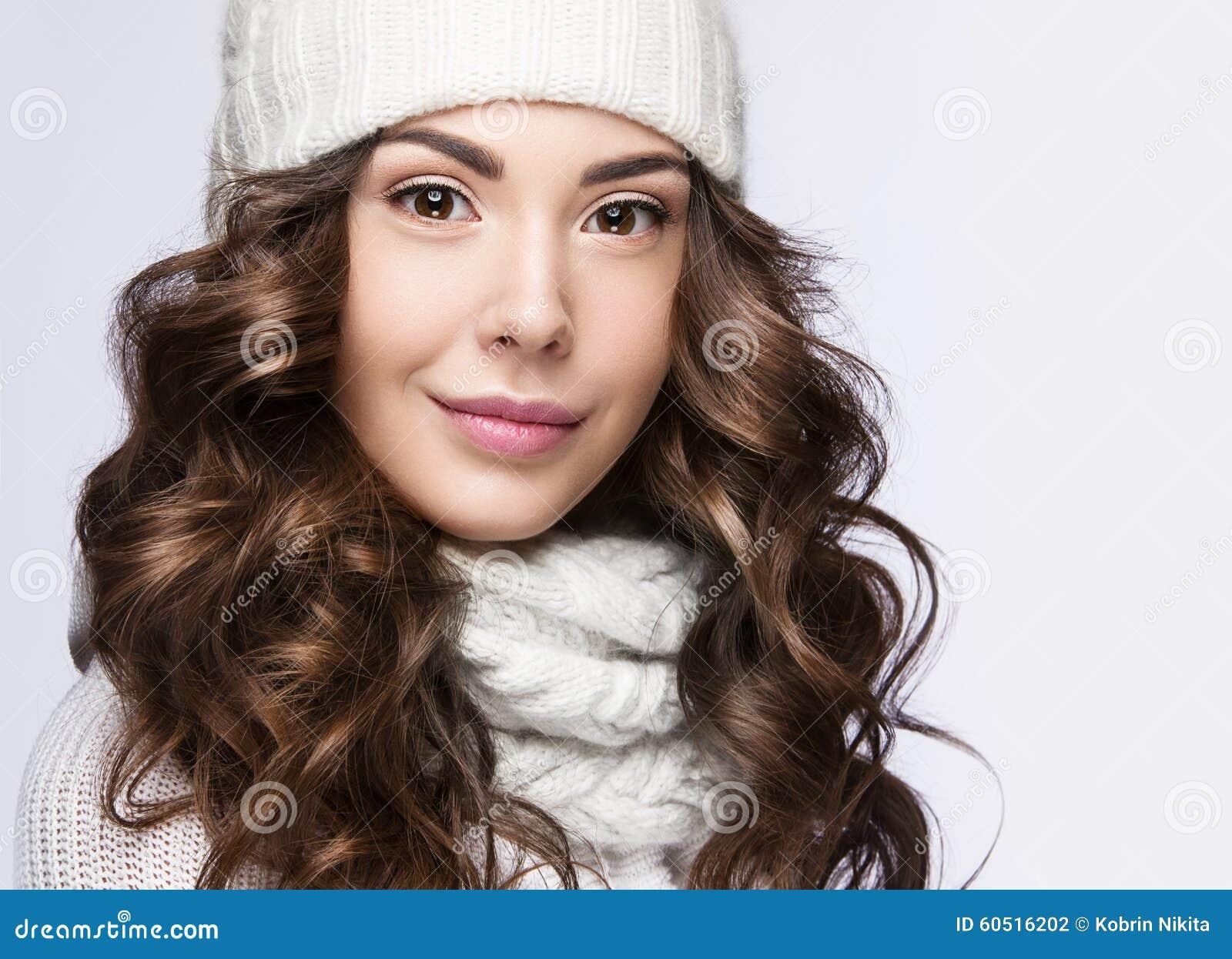 Het mooie meisje met zachte make up de krullen en de glimlach in wit breien hoed warm de - Beeld het meisje van ...