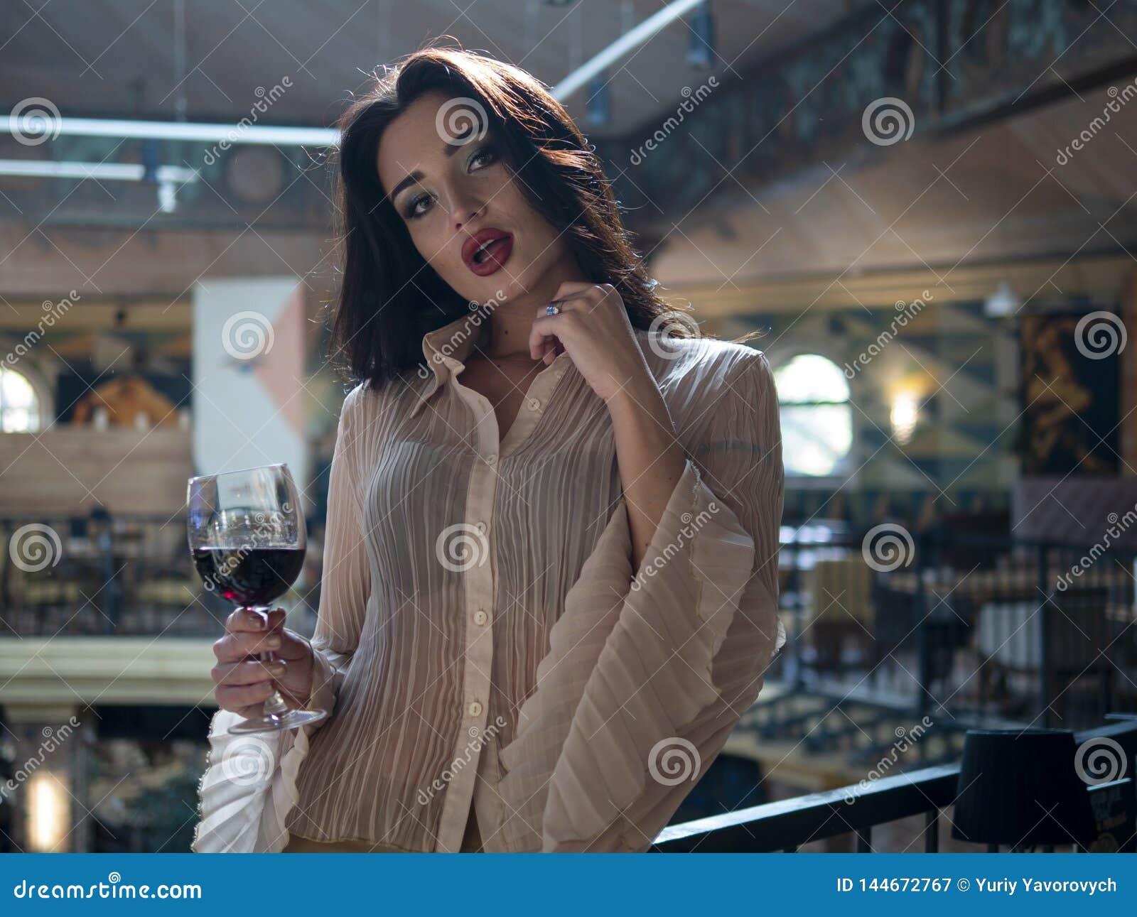 Het mooie meisje model stellen die zich met een glas rode wijn in haar bevinden dient een restaurant in