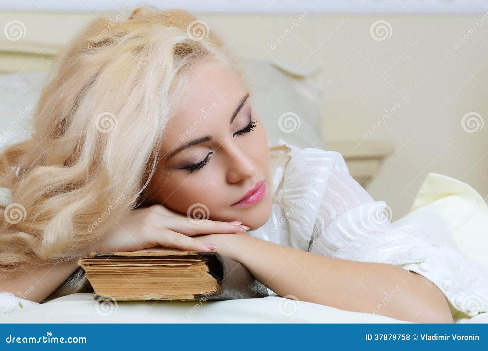Het mooie meisje op een bed