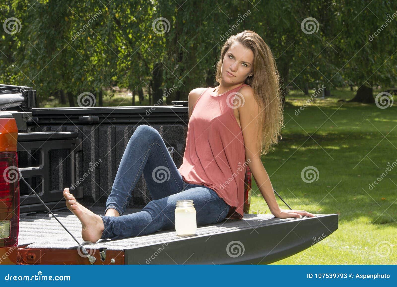 Het mooie meisje van het land op rug van oogstvrachtwagen