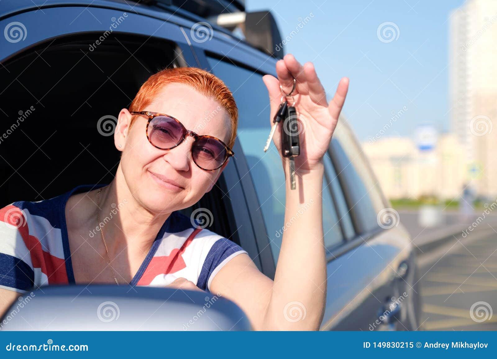 Het mooie meisje werd de gelukkige eigenaar van de nieuwe auto Houdt sleutels in zijn handen glimlachend aan het loensen van de z