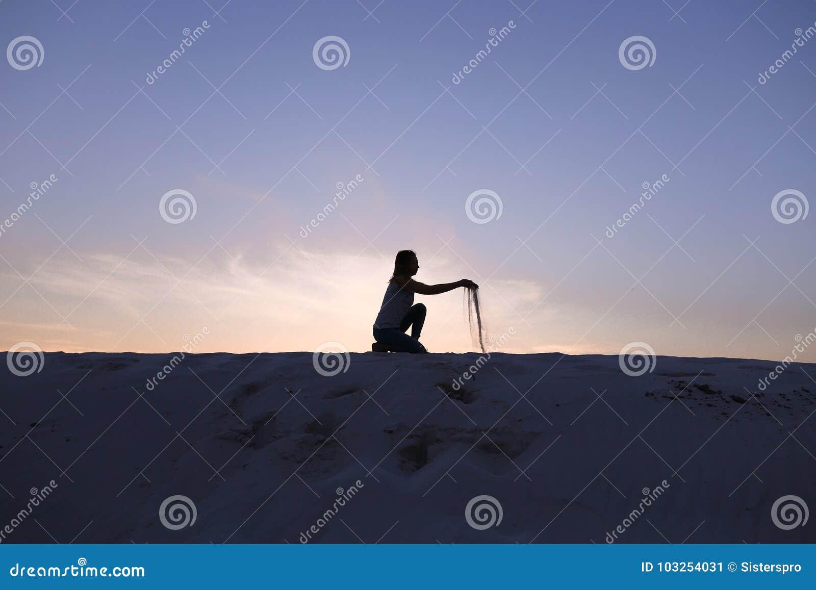 Het mooie meisje zit bij het buigen op zandige woestijnheuvel op zonsondergang
