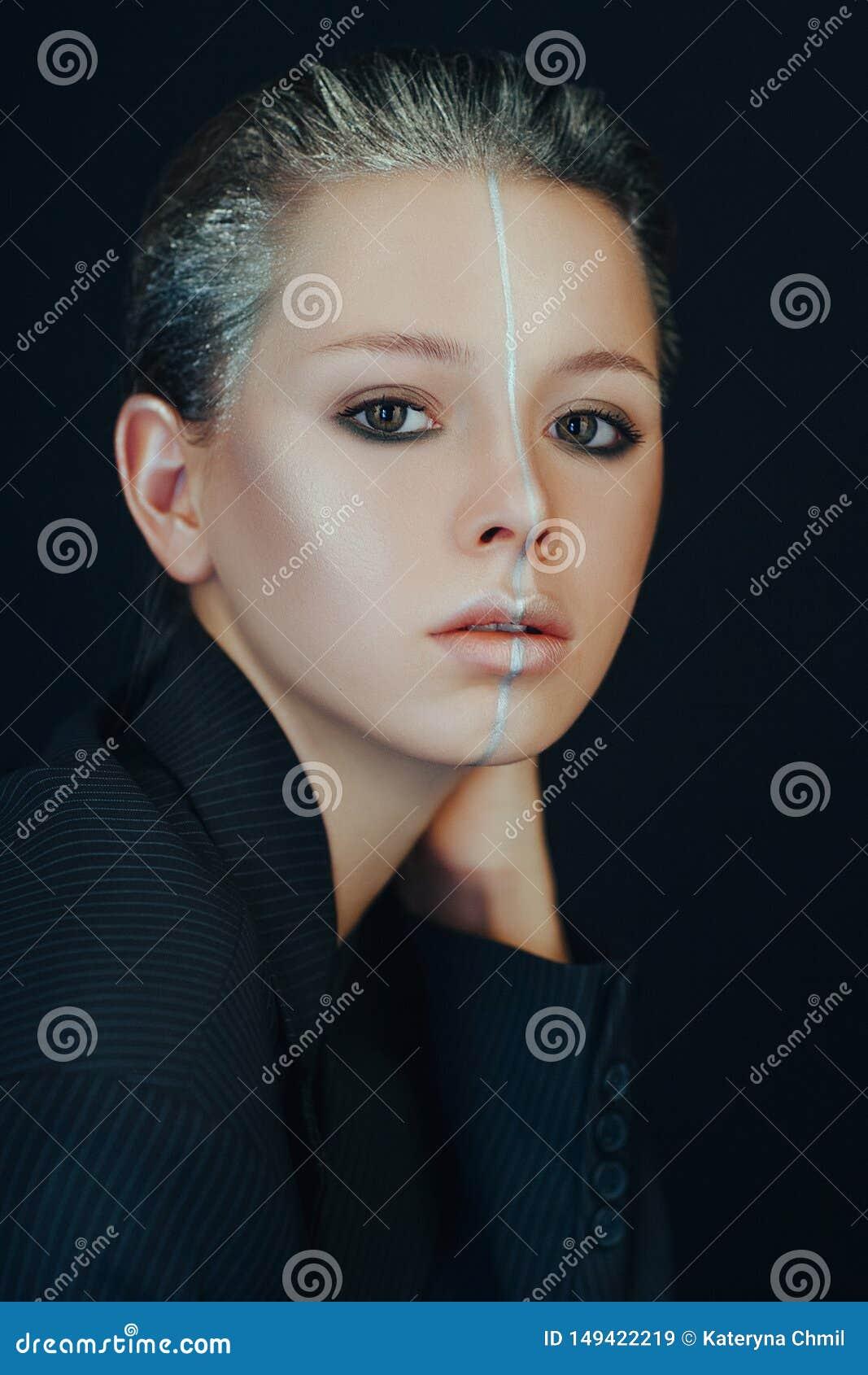 Het mooie model stelt in een badkamers met creatieve zilveren make-up