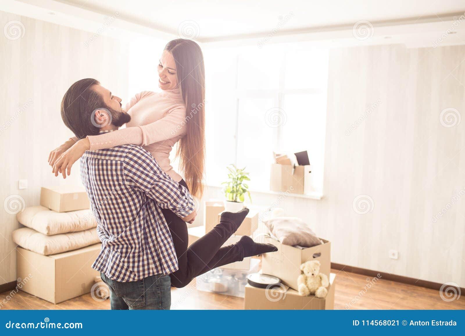 Het mooie paar bevindt zich in een heldere ruimte met uitgepakte dozen De jonge mens houdt zijn aantrekkelijke vrouw in handen