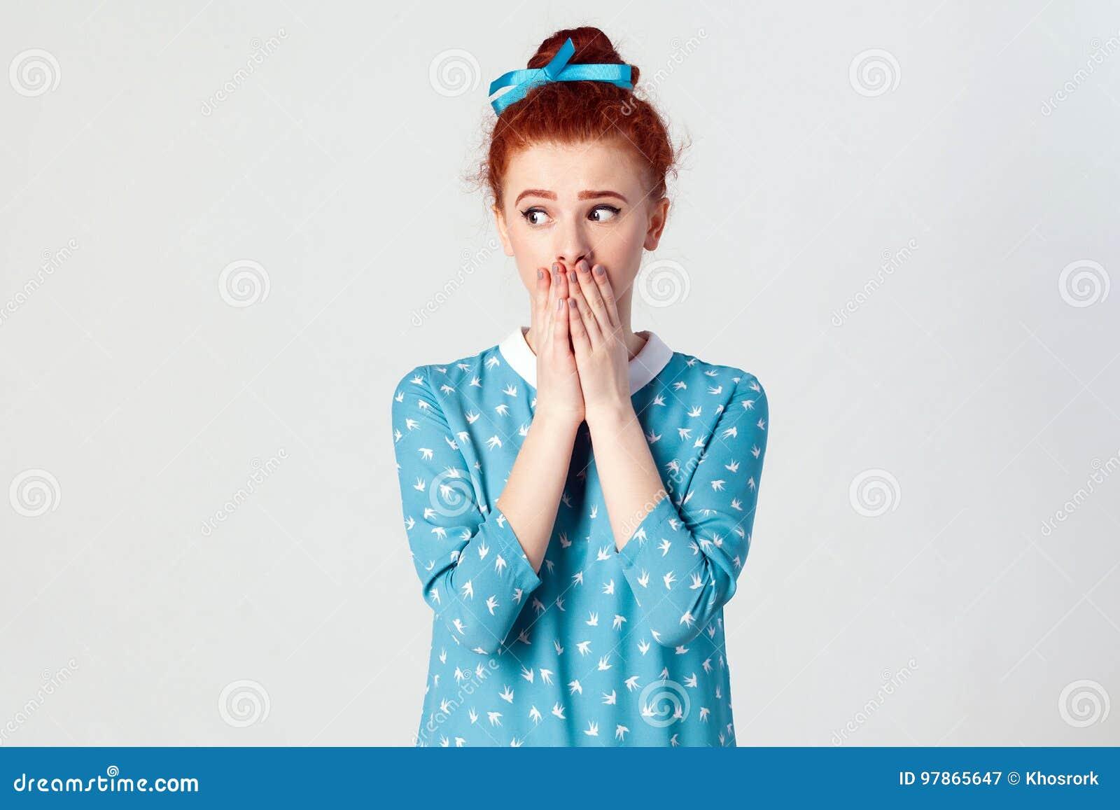 Het mooie roodharigemeisje in blauwe kleding doesn ` t wil geruchten of wat vertrouwelijke informatie uitspreiden