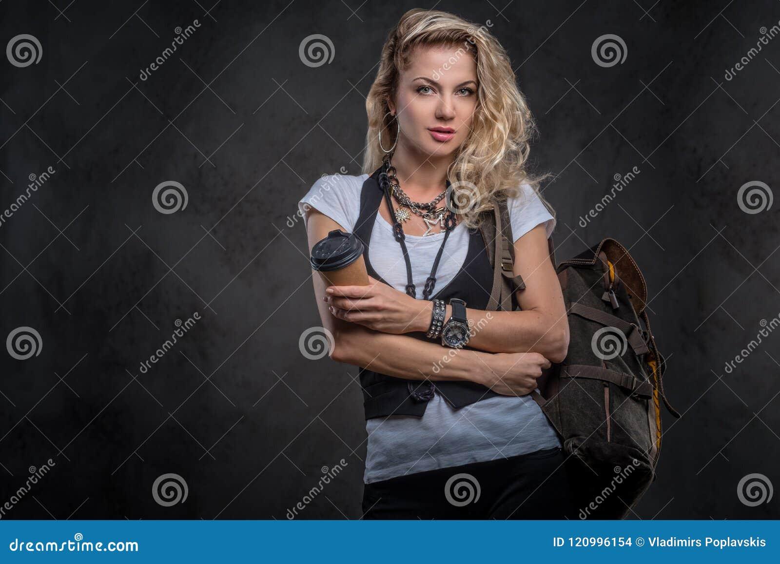 Het mooie toeristenmeisje gekleed in een wit t-shirt en een vest draagt heel wat toebehoren en polshorloge, die bevinden zich met