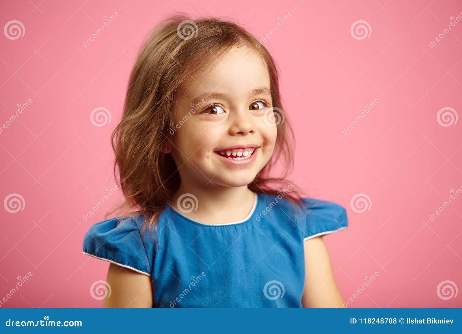 Het mooie verraste kindmeisje met leuke glimlach en oprecht kijkt, is in een goede stemming, drukt dichte vreugde en geluk uit,