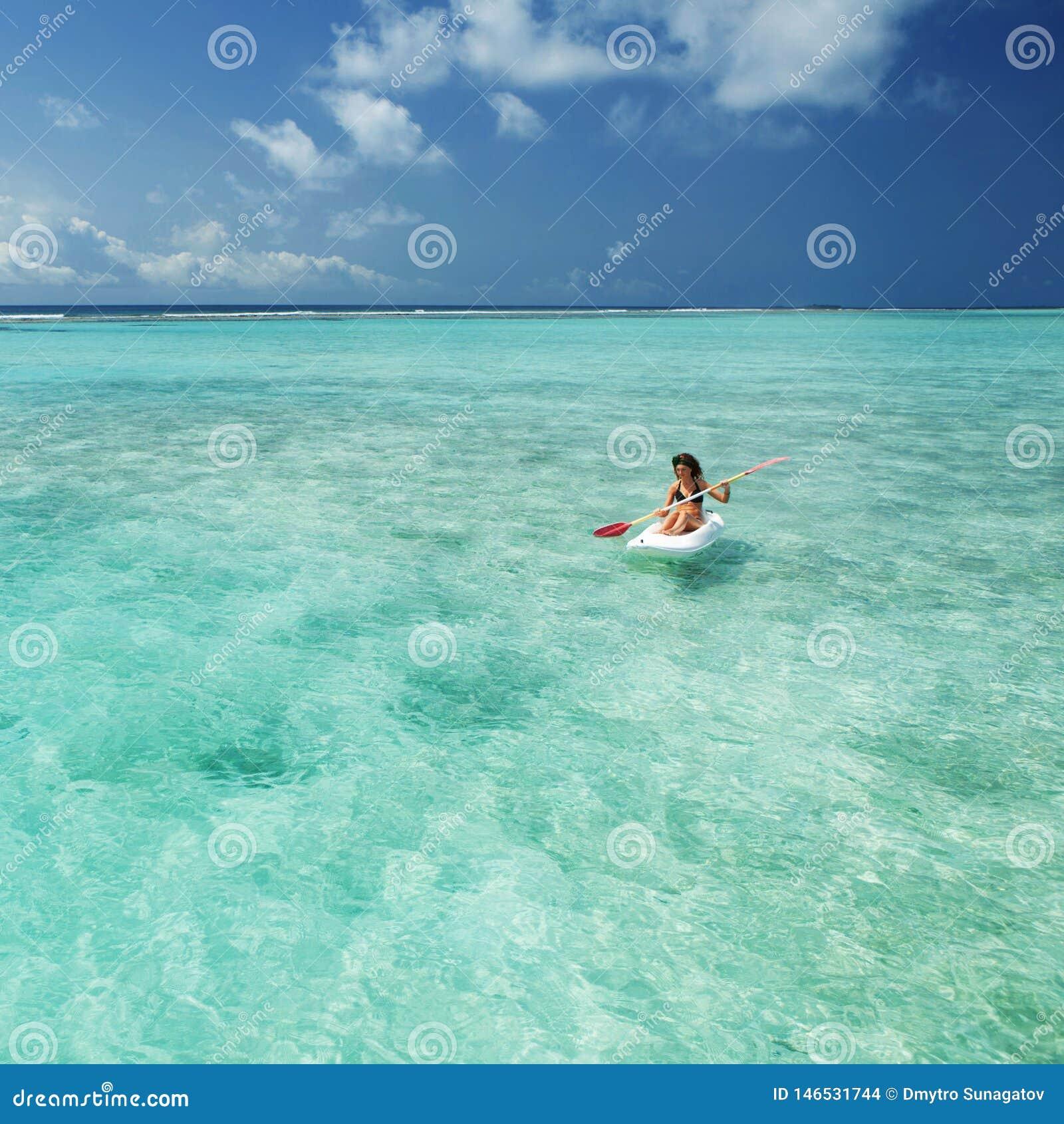 Het mooie vrouw zwemmen in kano en ontspant in het overzees Gelukkige eilandlevensstijl Wit zand, kristal-blauwe overzees van tro