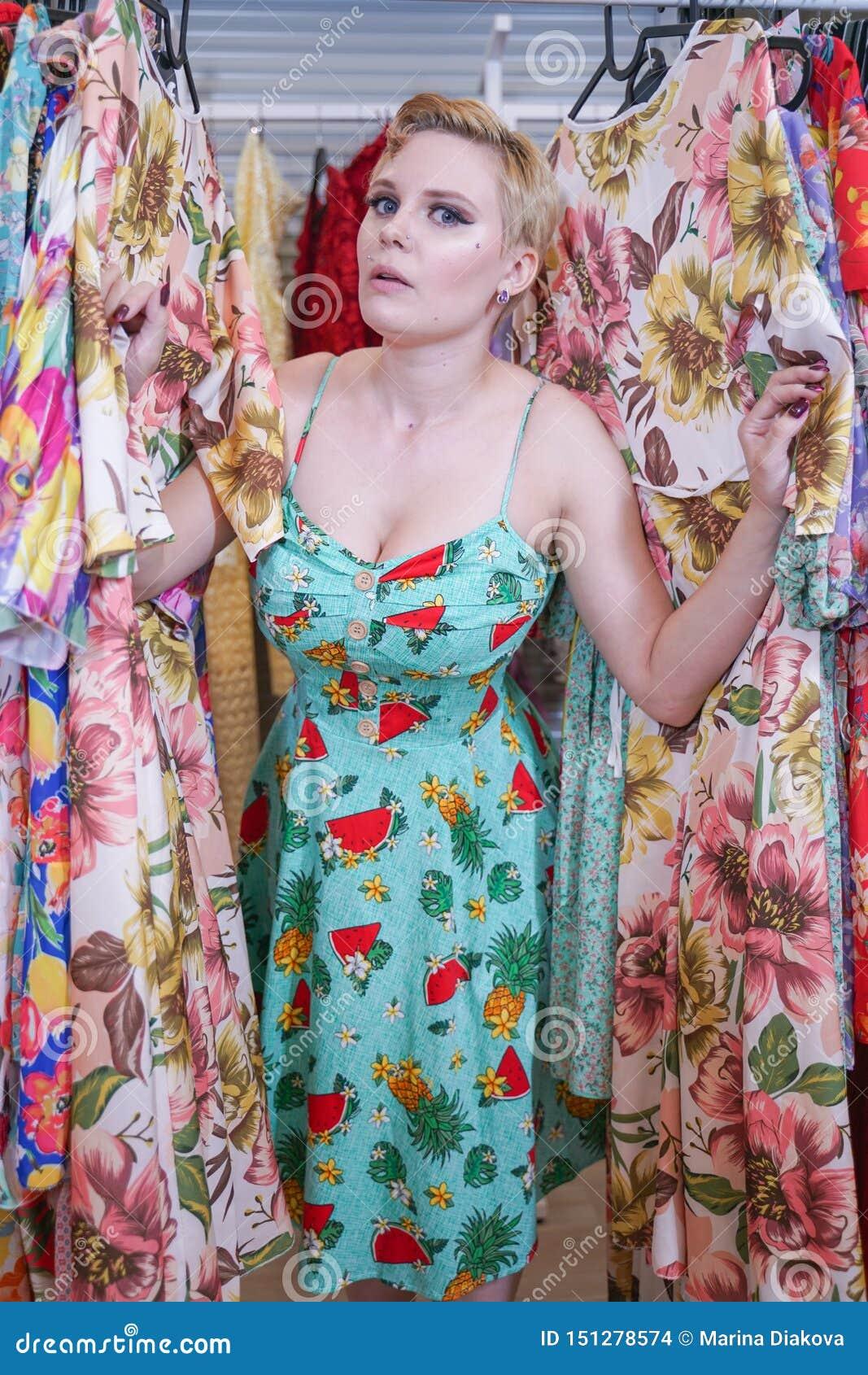 Het mooie weelderige meisje in een modieuze kleding die in de opslag lopen en kiest nieuwe kleren, binnen bekijkend in kostuums o