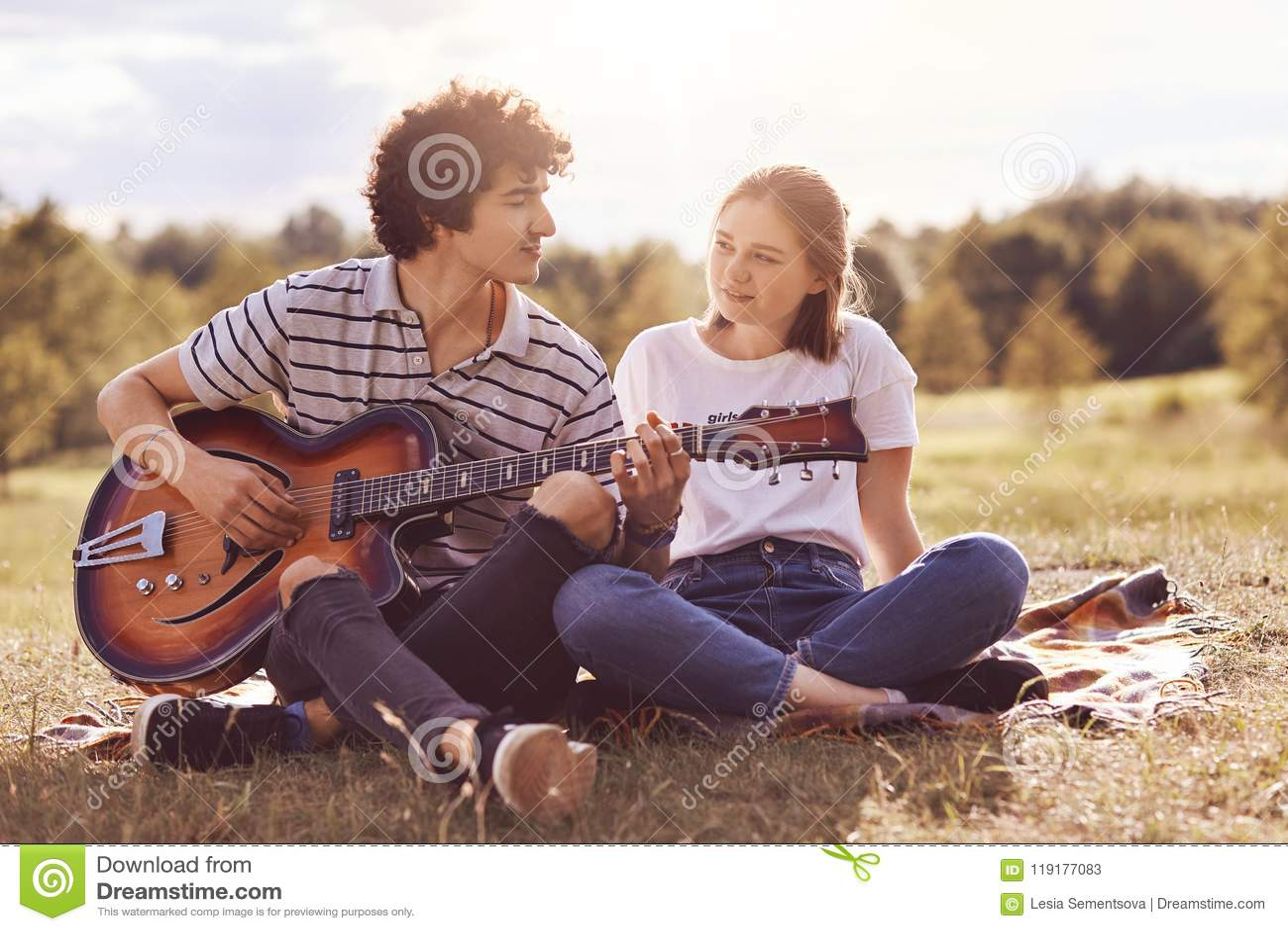 Het mooie wijfje bekijkt met liefde en geluk haar vriend die gitaar speelt en romantische liederen aan minnaar zingt, heeft unfor