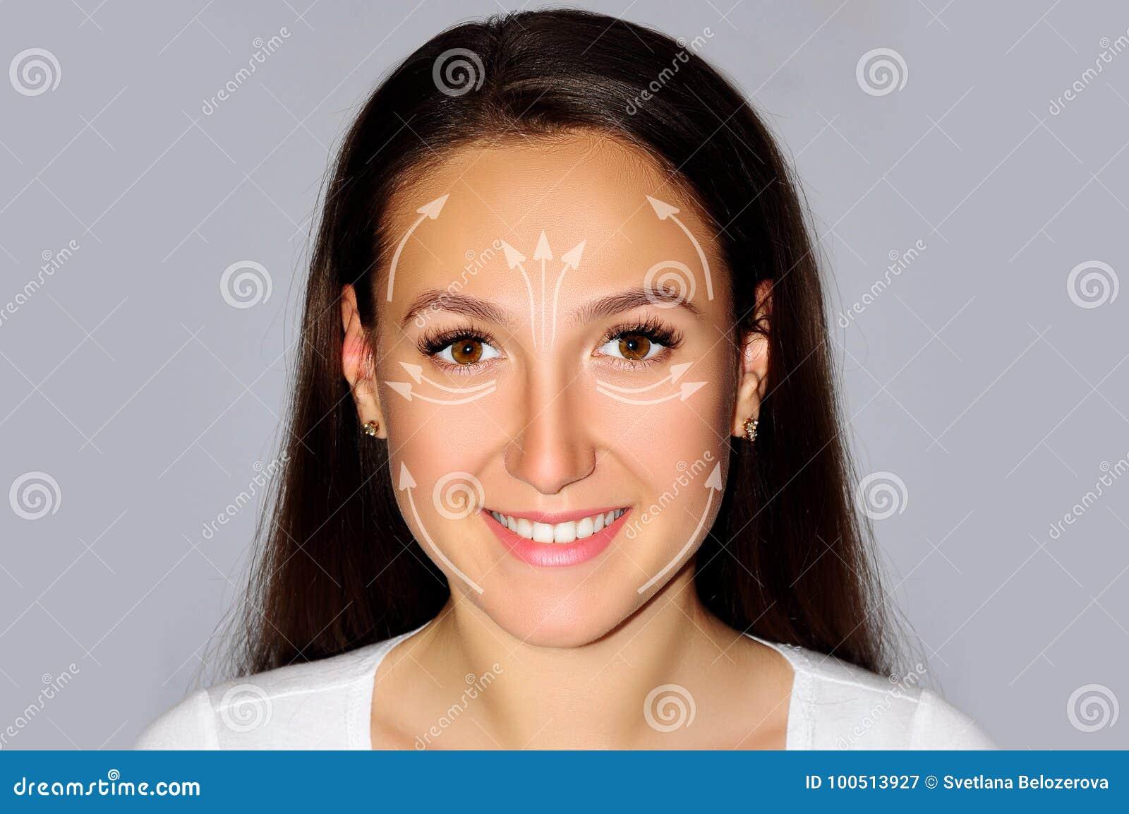 Het mooie wijfje van het close-upportret op grijze achtergrond, geïsoleerd gezicht het opheffen concept met de pijlengezondheid,