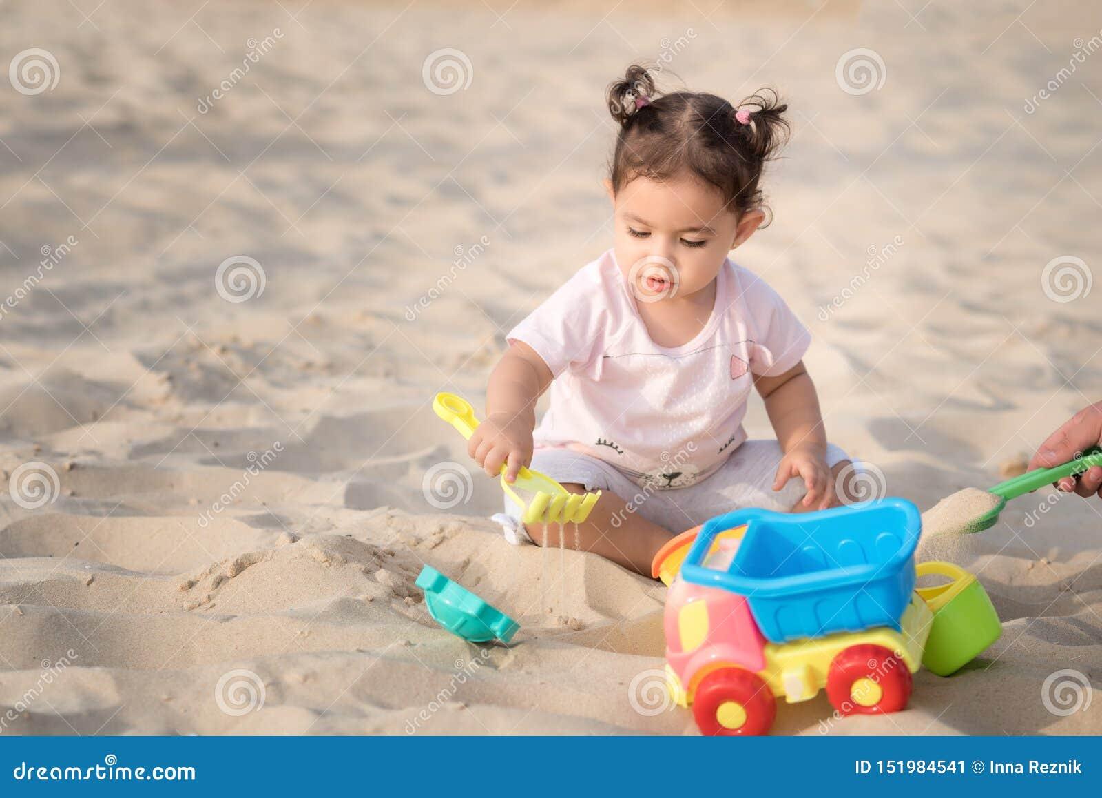 Het mooie zoete Babymeisje spelen op het zandige de zomerstrand dichtbij het overzees Reis en vakantie met kinderen