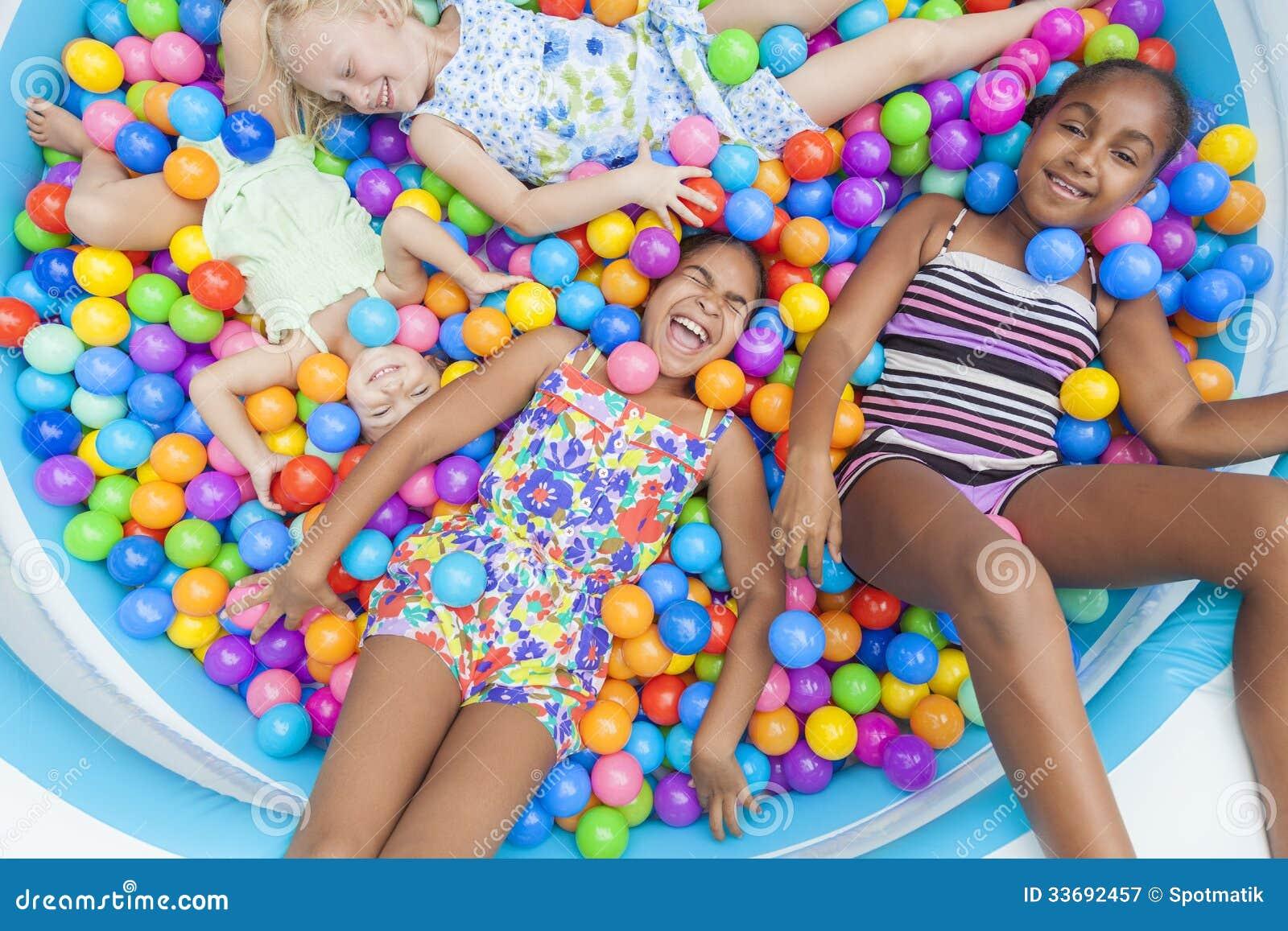Het multi Rassen de Pret van Meisjeskinderen Spelen in Gekleurde Balkuil