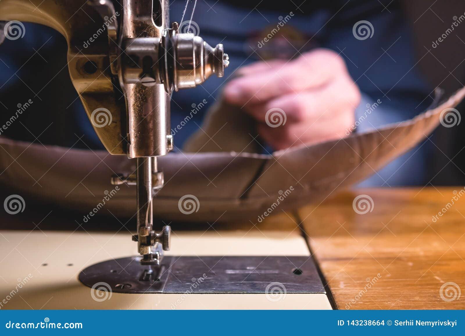 Het naaien proces van de leerriem oude Man handen achter het naaien Leerworkshop het textiel uitstekende industrieel naaien