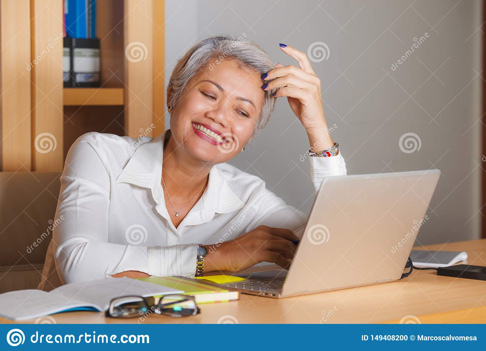 Het natuurlijke portret van het levensstijlbureau van het aantrekkelijke en gelukkige succesvolle rijpe Aziatische vrouw werken b
