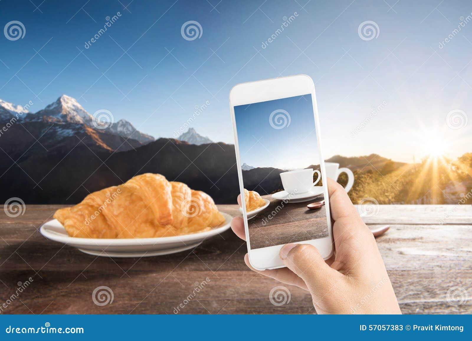 Het nemen van foto van verse gebakken croissants en koffie op houten Ta