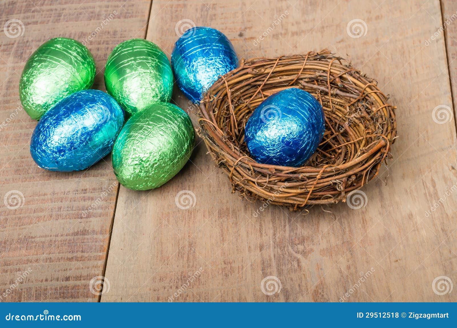Het nest van de kleine vogel met groene en blauwe folieeieren