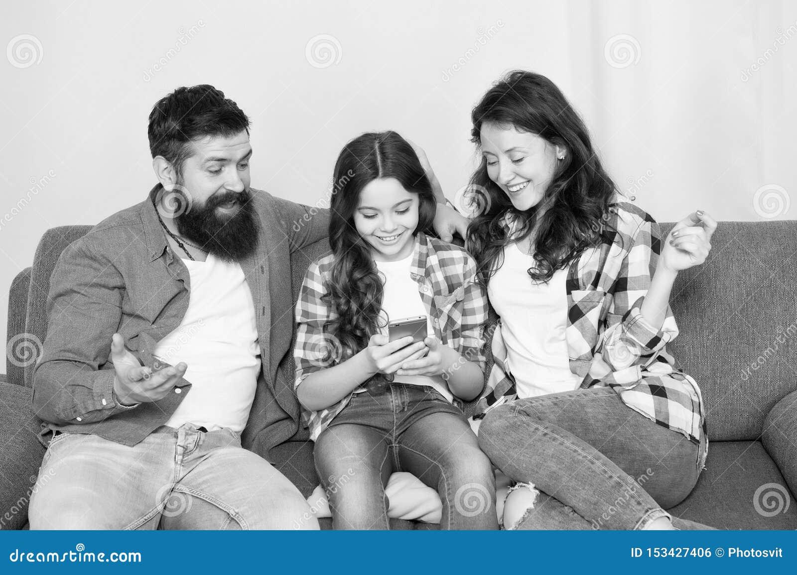 Het nieuws van het kindaandeel met moeder en vader Het gebruiks mobiele telefoon van het meisjekind Gelukkige Familie thuis Koop