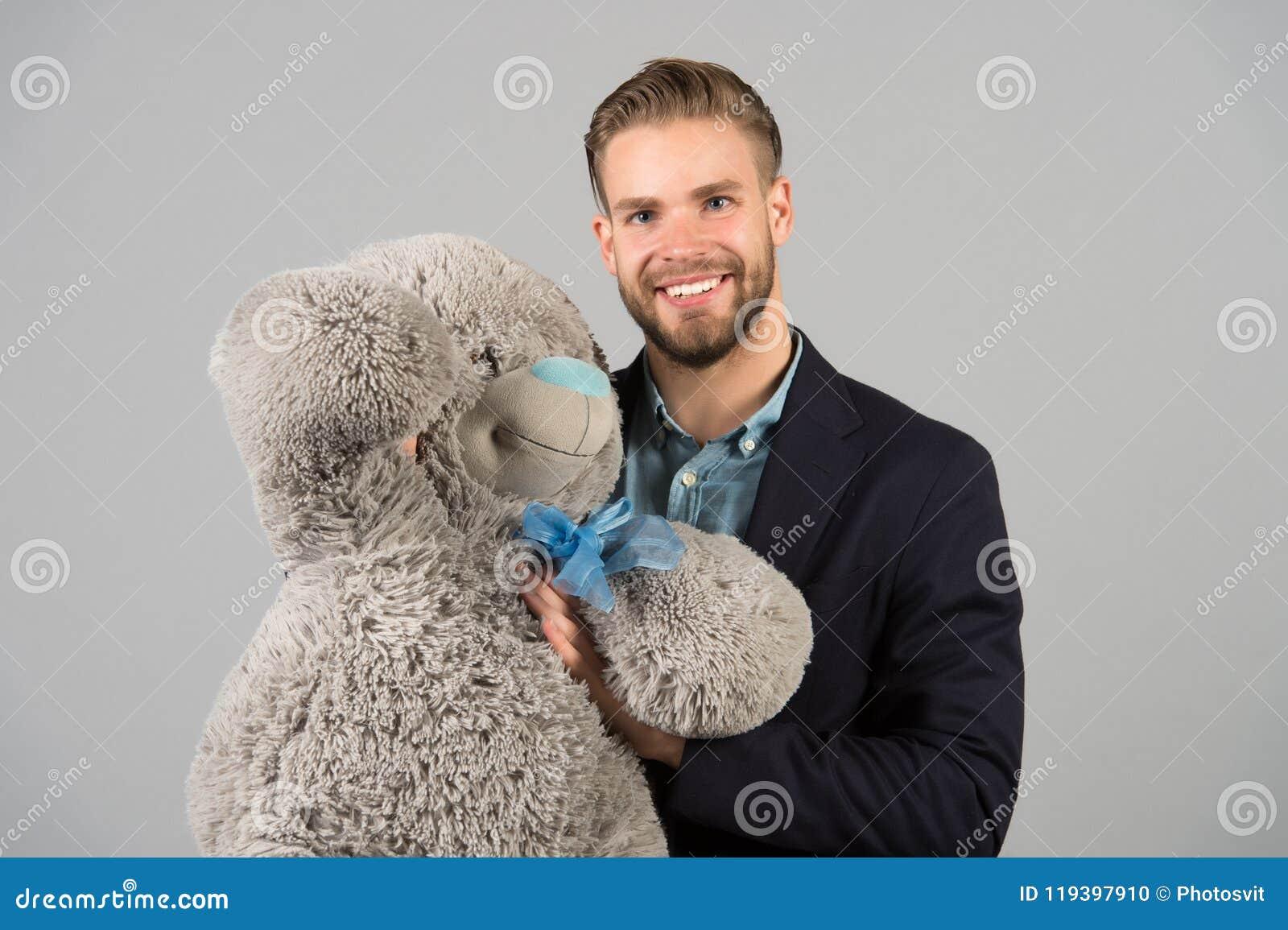 Het is nooit te laat om gelukkige volwassenheid te hebben Mensen hols grote teddybeer, grijze achtergrond Het concept van de verj