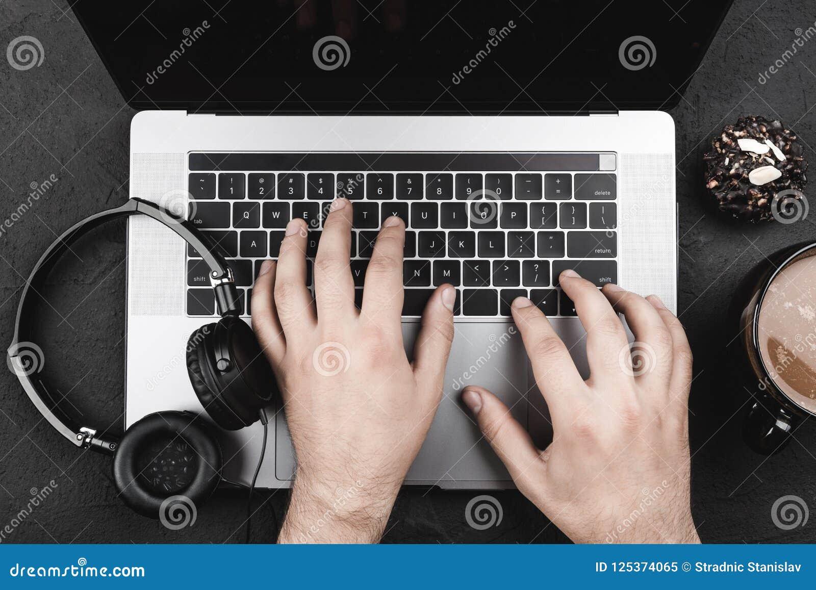 Het onderzoek van internetgebruiker` s handen naar een favoriet lied, laptop, hoofdtelefoons