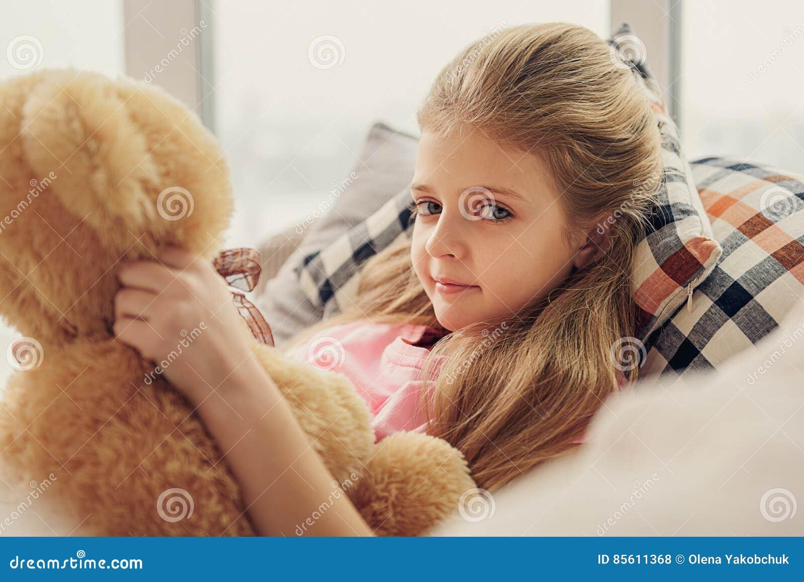 Het onschuldige meisje spelen met stuk speelgoed draagt