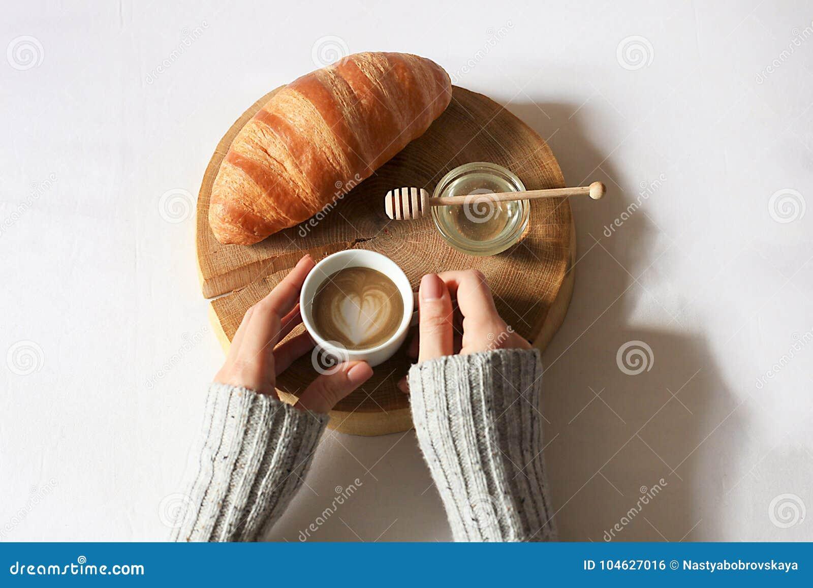 Download Het Ontbijt In Bedvlakte Lag De Holdingskop Van De Vrouwenhand Van Koffie, Houten Besnoeiing Met Vers Croissant En Honing In Bed Stock Foto - Afbeelding bestaande uit achtergrond, bakkerij: 104627016