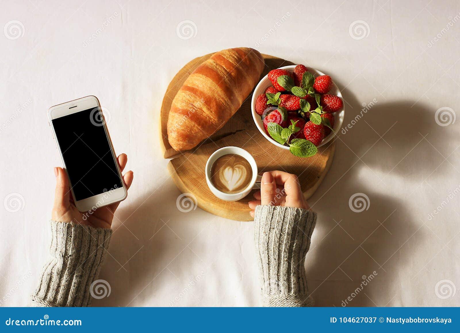 Download Het Ontbijt In Bedvlakte Lag Vrouwenhanden Die Kop Van Koffie En Telefoon, Houten Besnoeiing Met Vers Croissant En Aardbei In Bed Stock Afbeelding - Afbeelding bestaande uit life, croissant: 104627037