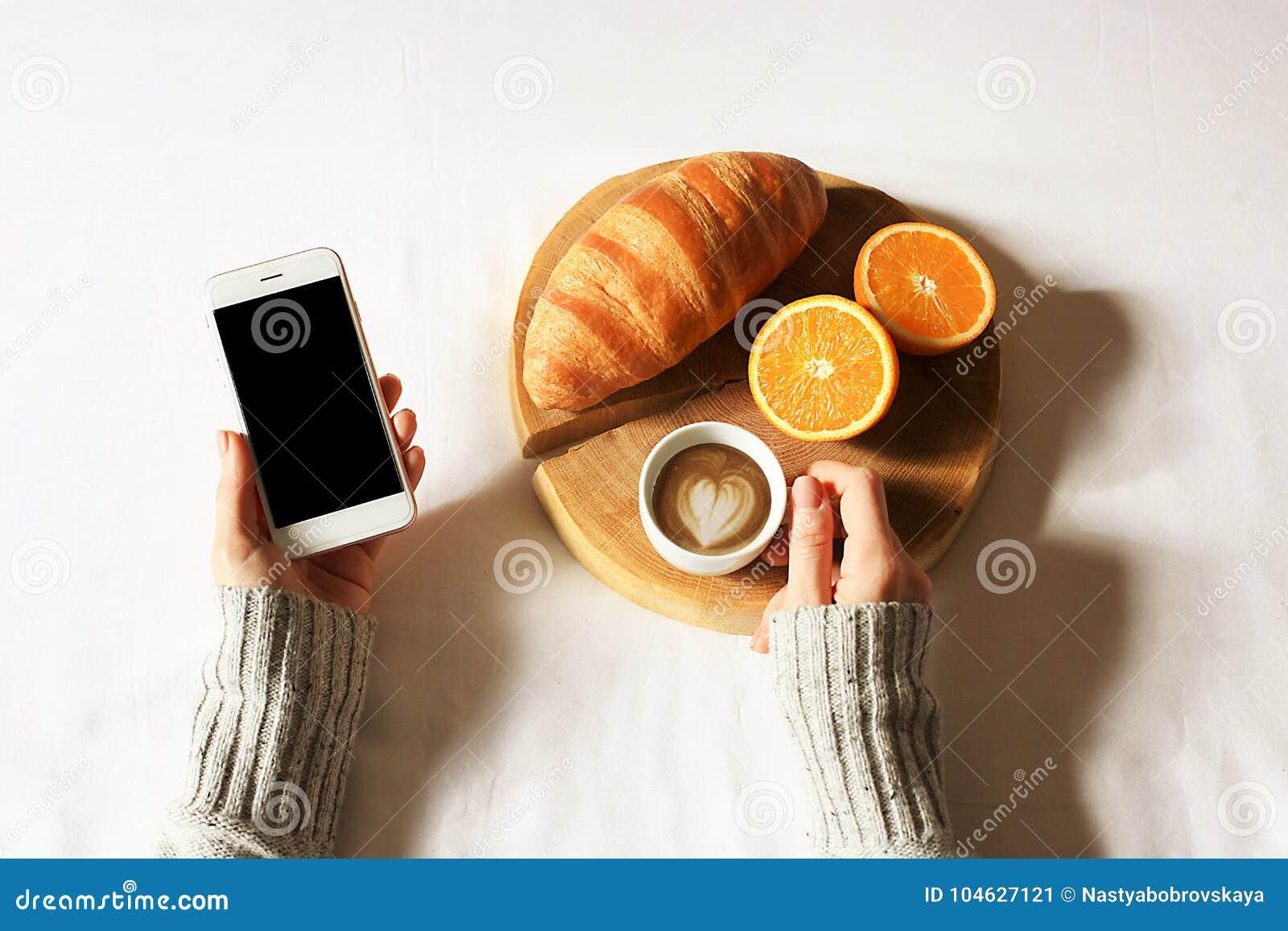Download Het Ontbijt In Bedvlakte Lag Vrouwenhanden Die Kop Van Koffie En Telefoon, Houten Besnoeiing Met Vers Croissant En Aardbei In Bed Stock Afbeelding - Afbeelding bestaande uit croissant, fruit: 104627121