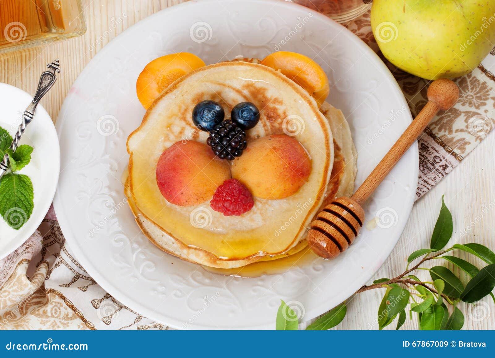 Het ontbijtpannekoeken die van kinderen gezicht van de de aardbeibosbes van de babyteddybeer en de abrikoos, leuk voedsel, honing